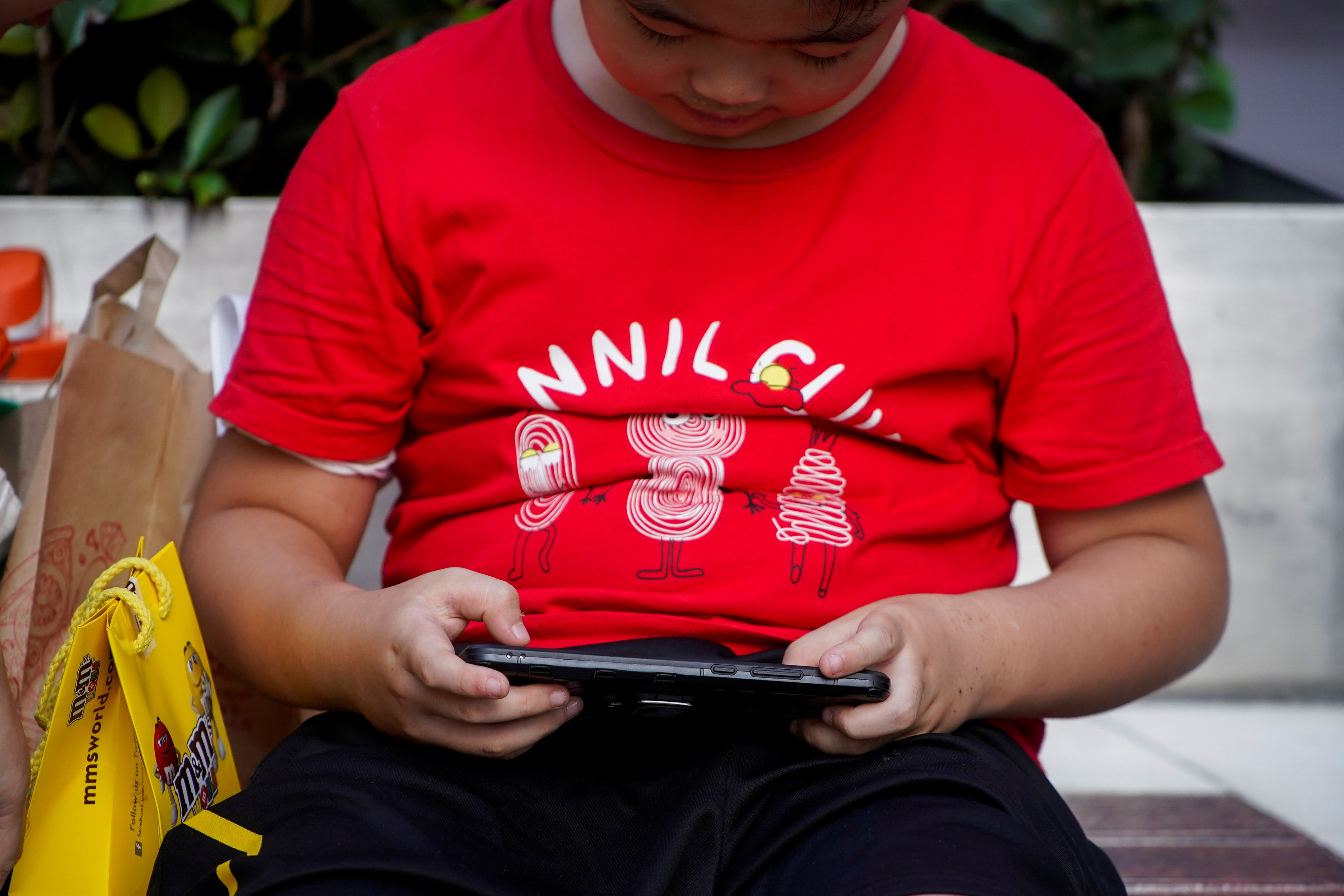 A boy plays a game on a phone on a street in Shanghai, China August 31, 2021. REUTERS/Aly Song