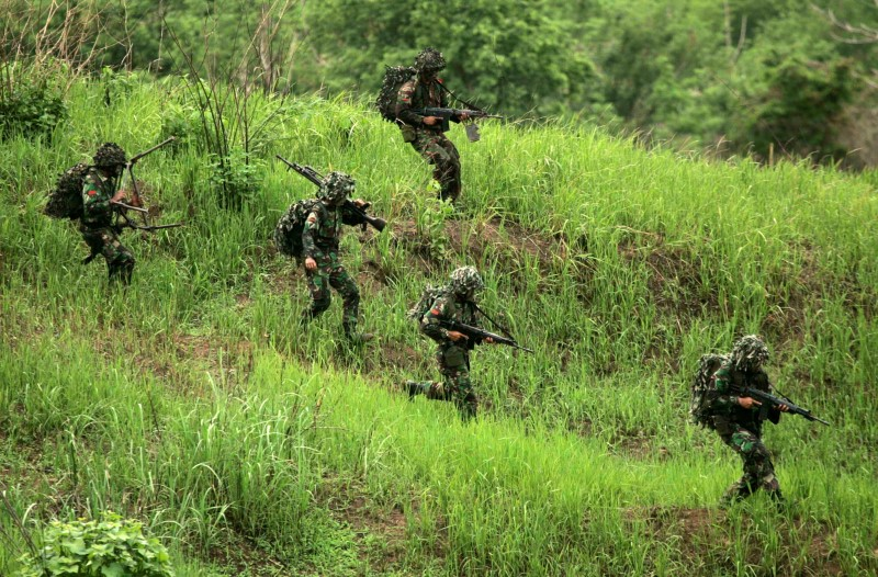 Indonesian army soldiers carry their weapons during the last day of a seven-day training exercise in Sukabumi, West Java province December 6, 2006.  REUTERS/Crack Palinggi/File Photo