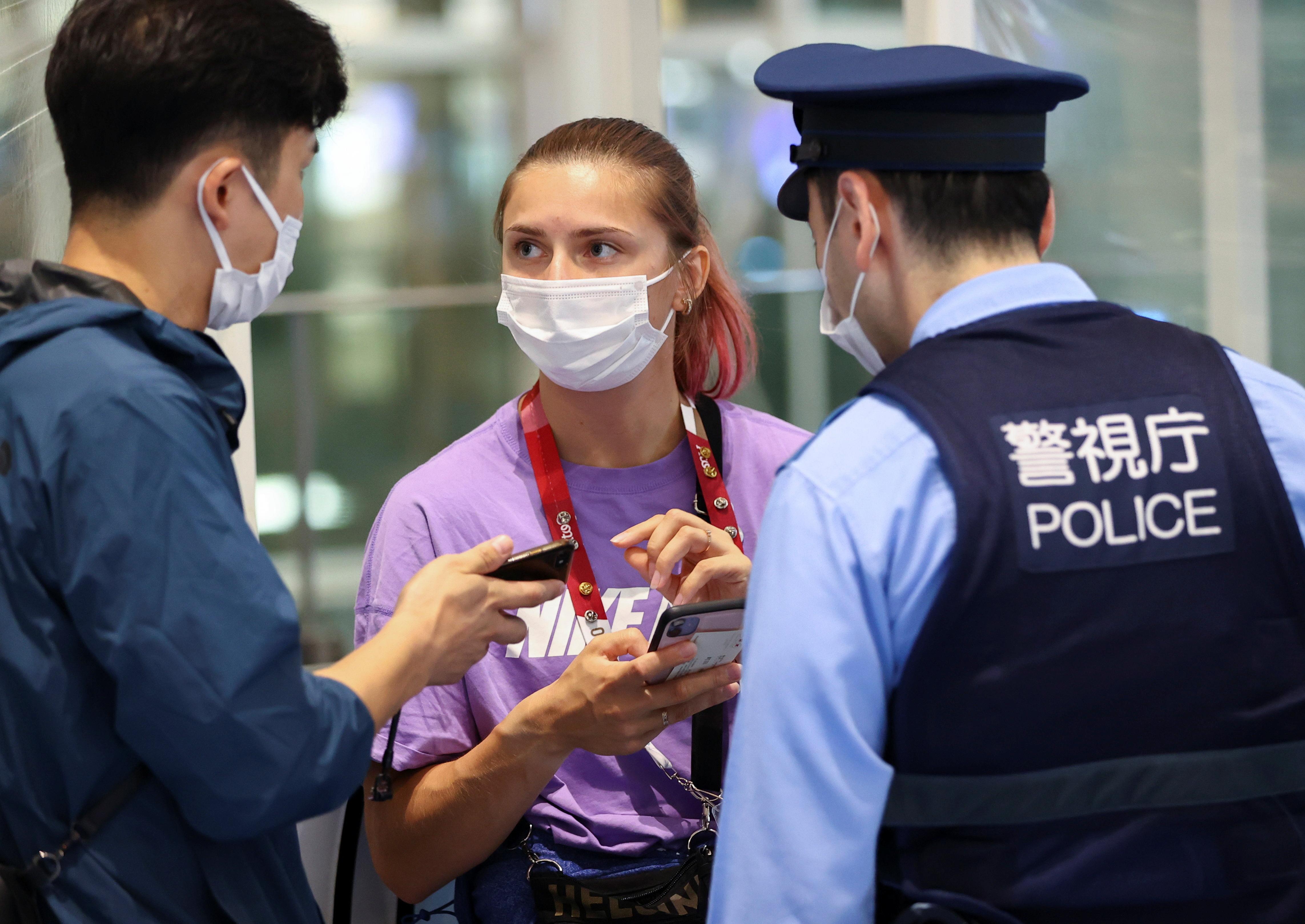 Belarusian athlete Krystsina Tsimanouskaya talks with a police officer at Haneda international airport in Tokyo, Japan August 1, 2021.  REUTERS/Issei Kato