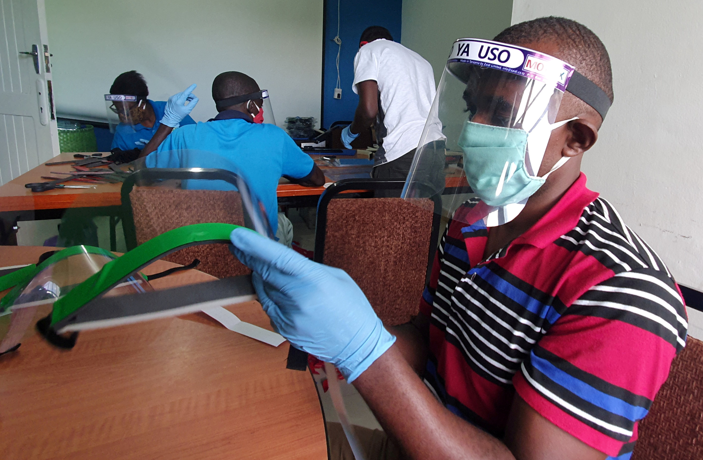 Workers prepare face shields from recycled plastics at the Zaidi Recyclers workshop as a measure to stop the spread of coronavirus disease (COVID-19) in Dar es Salaam, Tanzania May 27, 2020. REUTERS/Stringer/File Photo