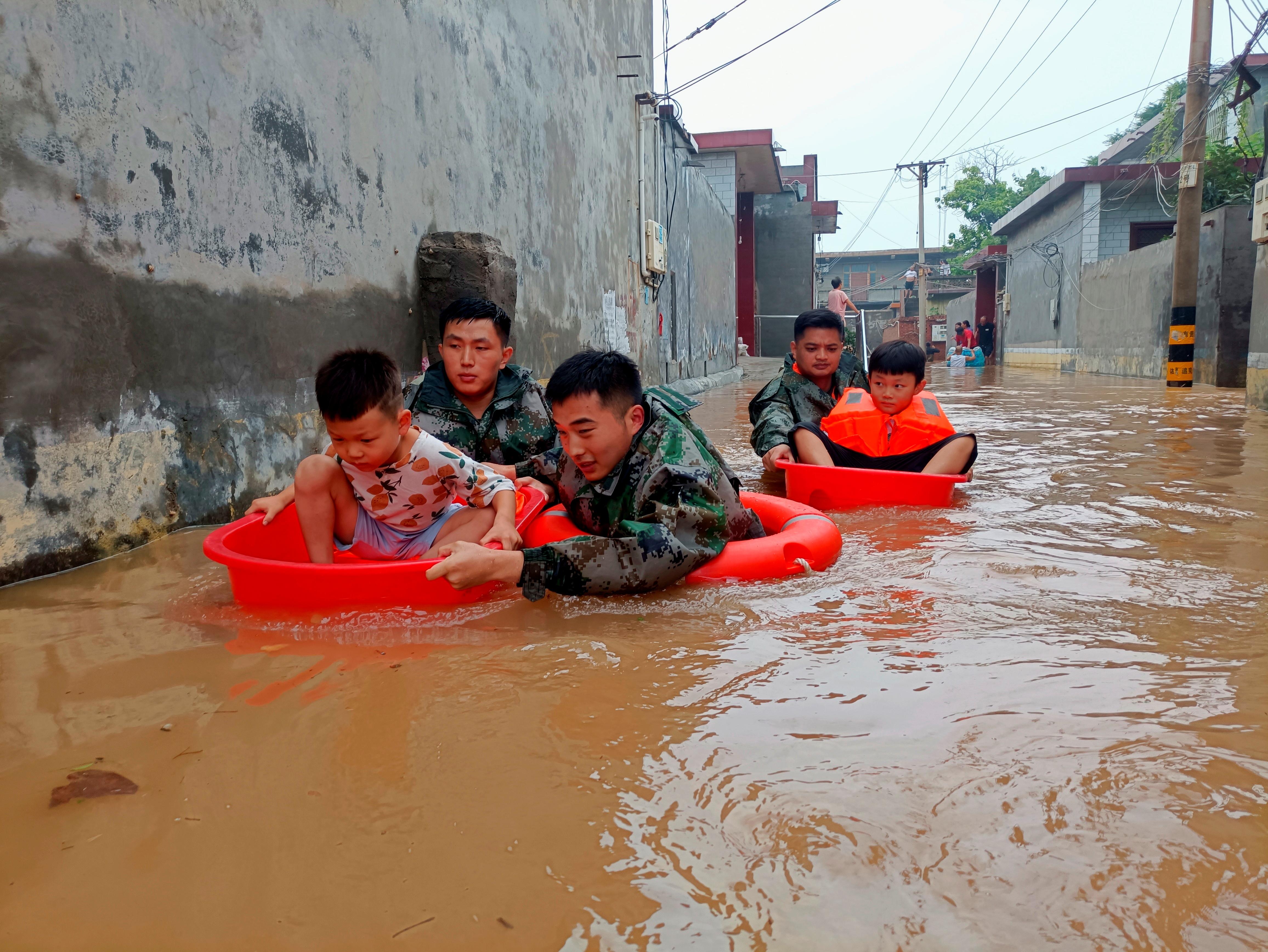 Các binh sĩ của Quân đội Giải phóng Nhân dân Trung Quốc (PLA) sơ tán trẻ em bị mắc kẹt trong nước lũ tại các lưu vực ở Weihui thuộc Tân Hương, tỉnh Hà Nam, Trung Quốc ngày 22 tháng 7 năm 2021. Hình ảnh chụp ngày 22 tháng 7 năm 2021. cnsphoto qua REUTERS ATTENTION EDITORS - HÌNH ẢNH NÀY ĐƯỢC CUNG CẤP BỞI THỨ BA BUỔI TIỆC.  TRUNG QUỐC RA ĐỜI.
