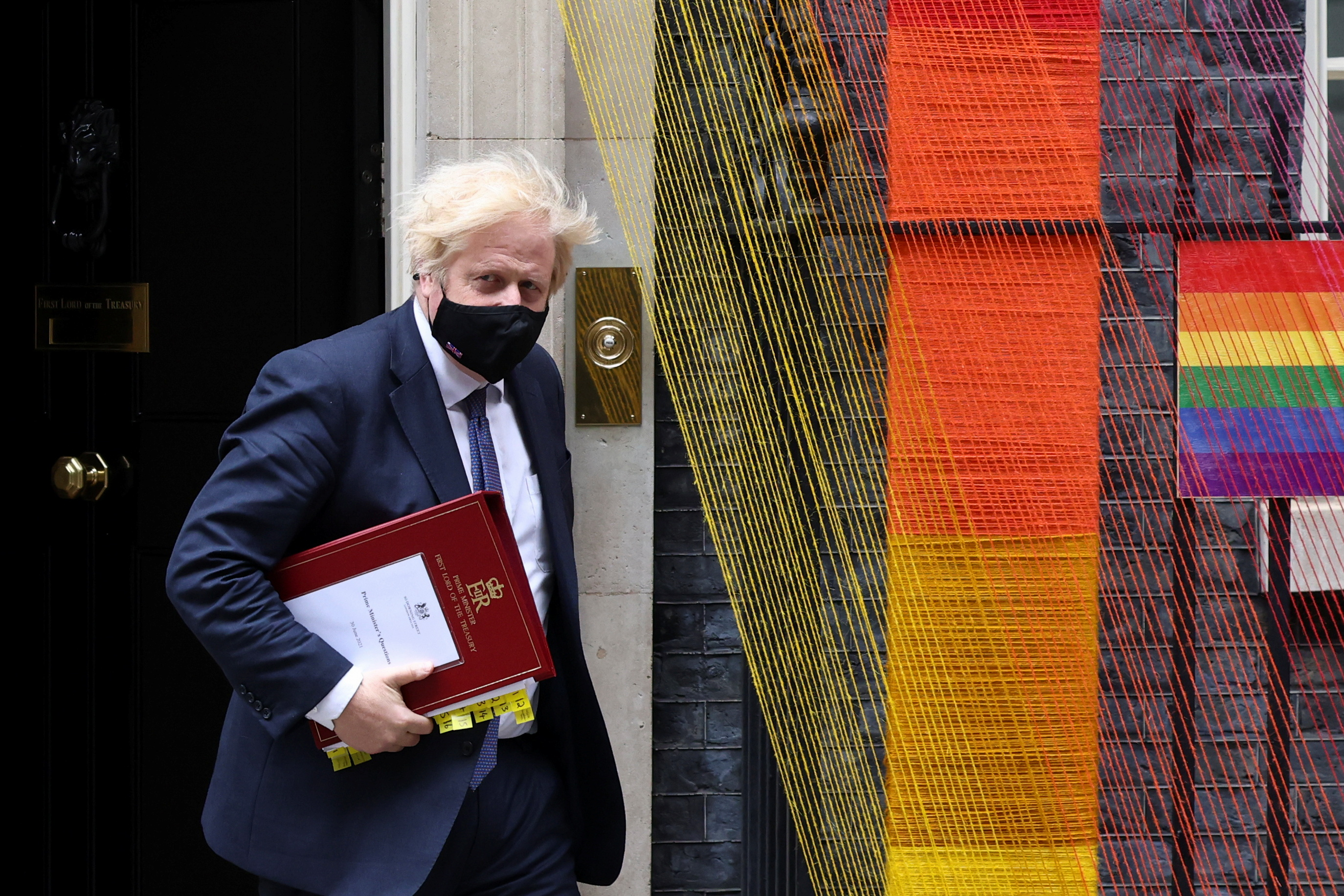 Britain's Prime Minister Boris Johnson walks past a rainbow arch by Artists Louisa Loizeau and Hattie Newman that has been installed over the door at Number 10 Downing Street, in London, Britain, June 30, 2021. REUTERS/Henry Nicholls