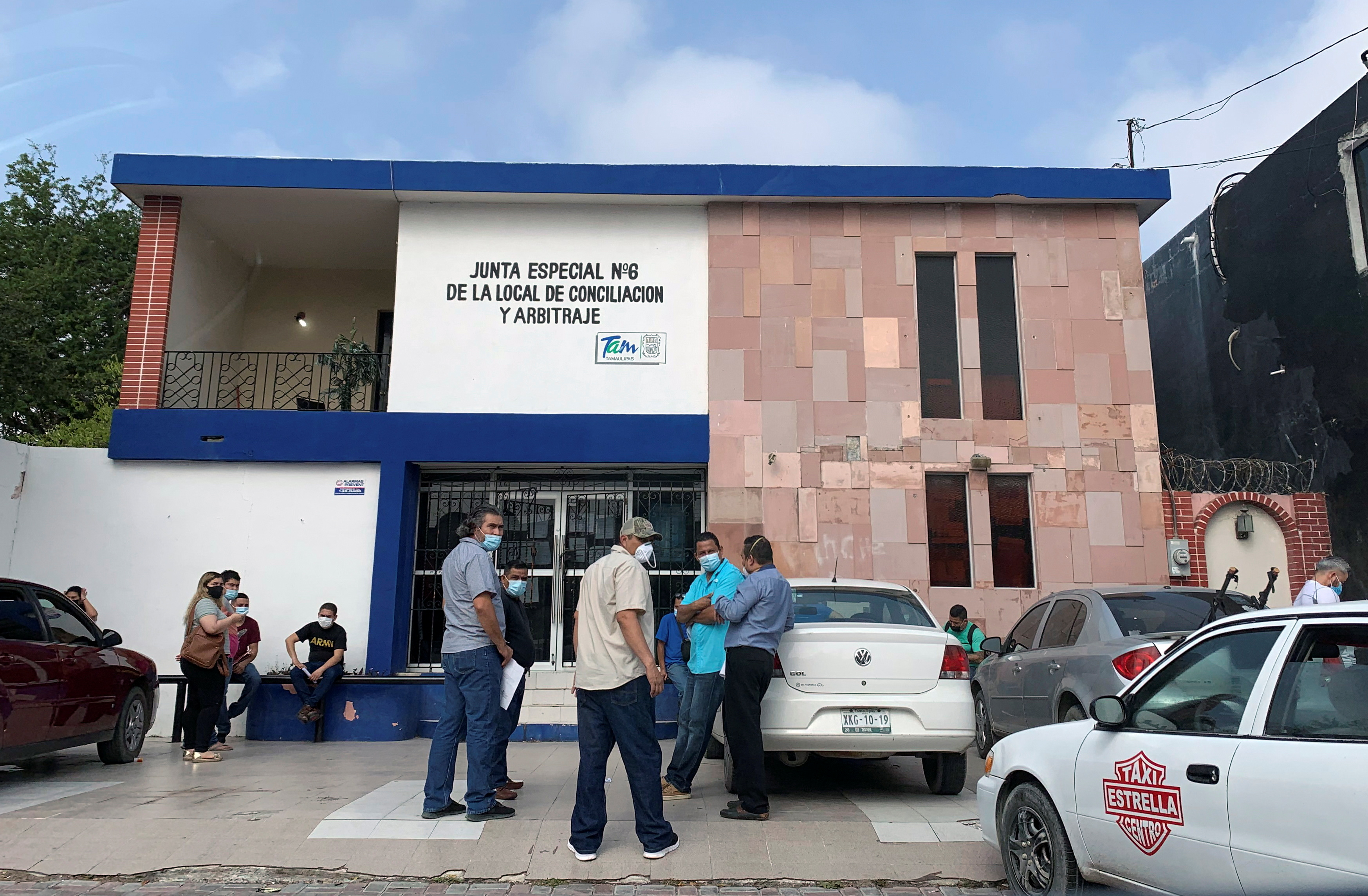 Workers aiming to resolve labor disputes wait outside a Conciliation and Arbitration Board, in Matamoros, Mexico January 26, 2021. REUTERS/Daina Solomon