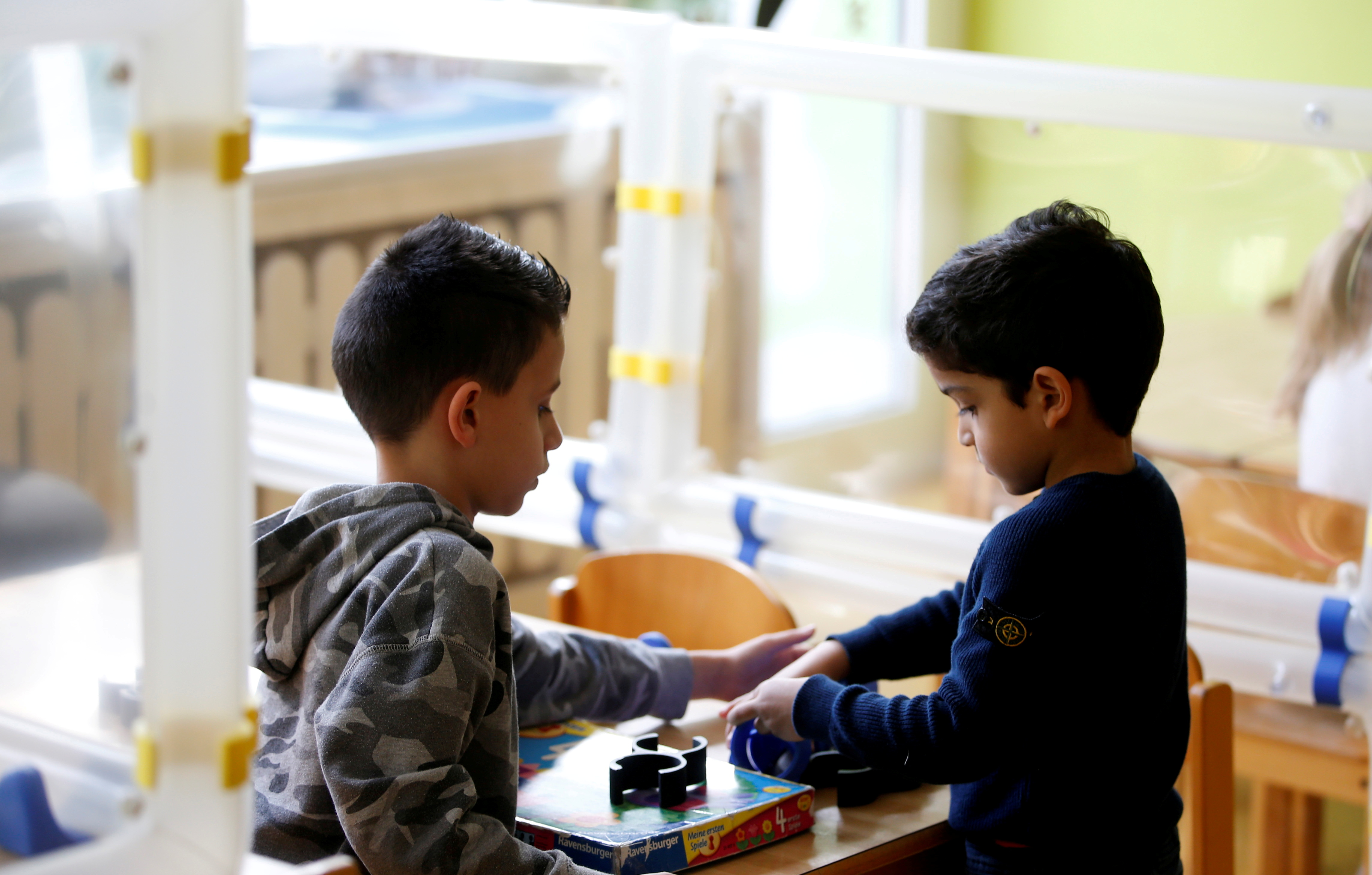 Children play at their tables during a demonstration of the use of sneeze guards at a nursery school as the spread of the coronavirus disease (COVID-19) continues, Velbert, Germany, April 8, 2021. REUTERS/Leon Kuegeler
