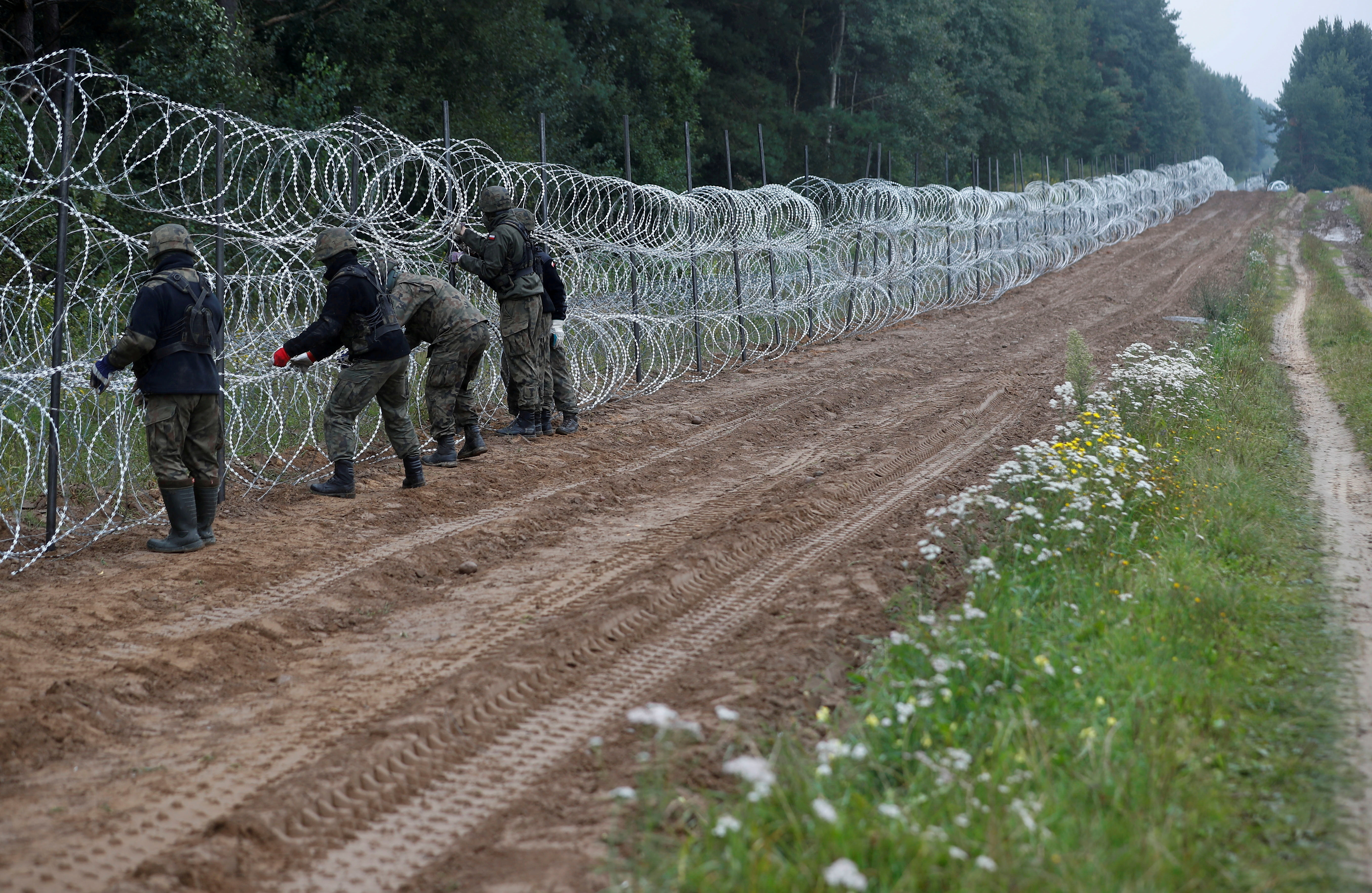 Polish soldiers build a fence on the border between Poland and Belarus near the village of Nomiki, Poland August 26, 2021. REUTERS/Kacper Pempel/File Photo