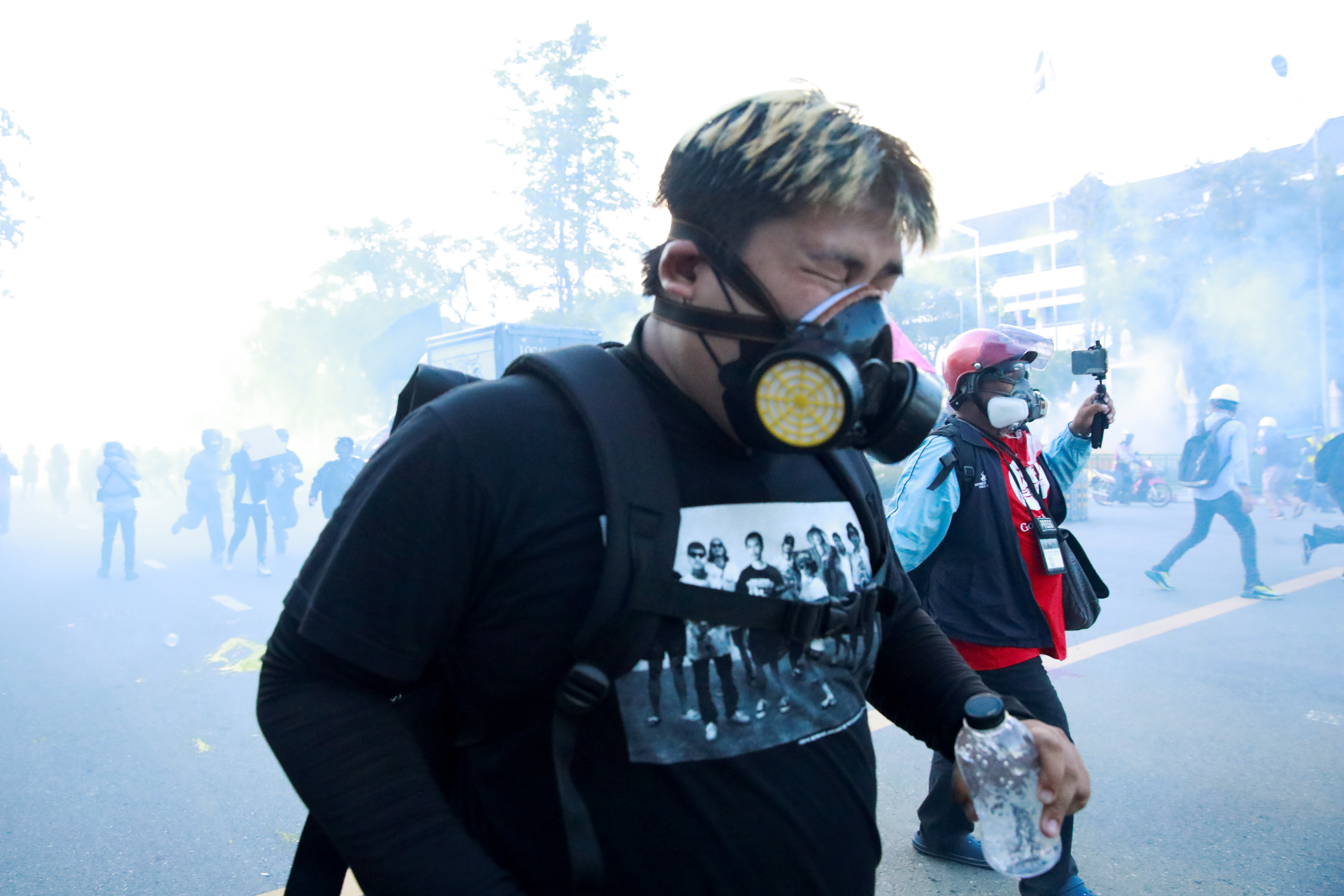 A man reacts among tear gas during a protest over the government's handling of the coronavirus disease (COVID-19) pandemic, in Bangkok, Thailand, August 16, 2021. REUTERS/Soe Zeya Tun