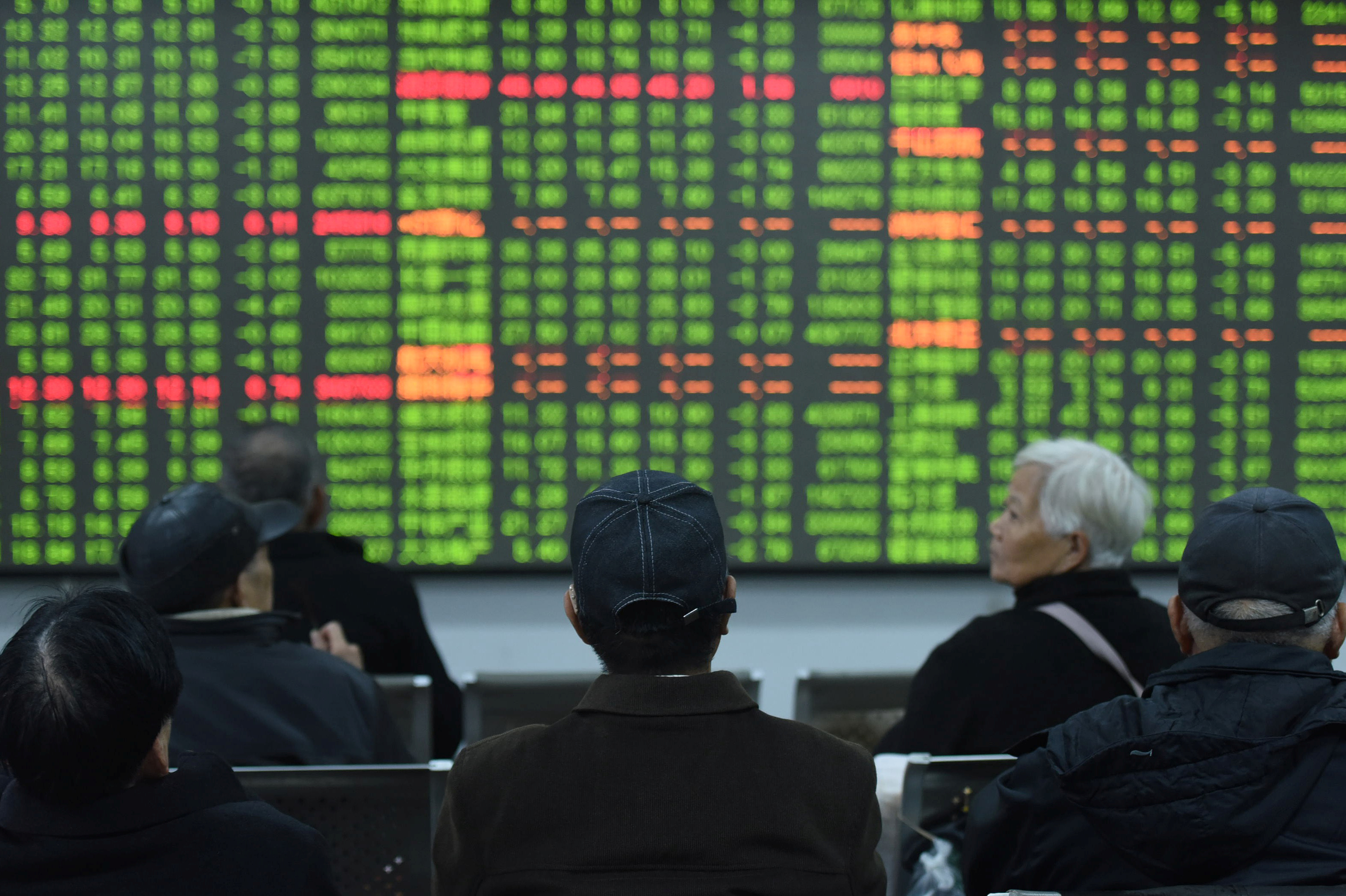 Investors sit in front of a board showing stock information at a brokerage house on the first day of trade in China since the Lunar New Year, in Hangzhou, Zhejiang province, China February 3, 2020. China Daily via REUTERS