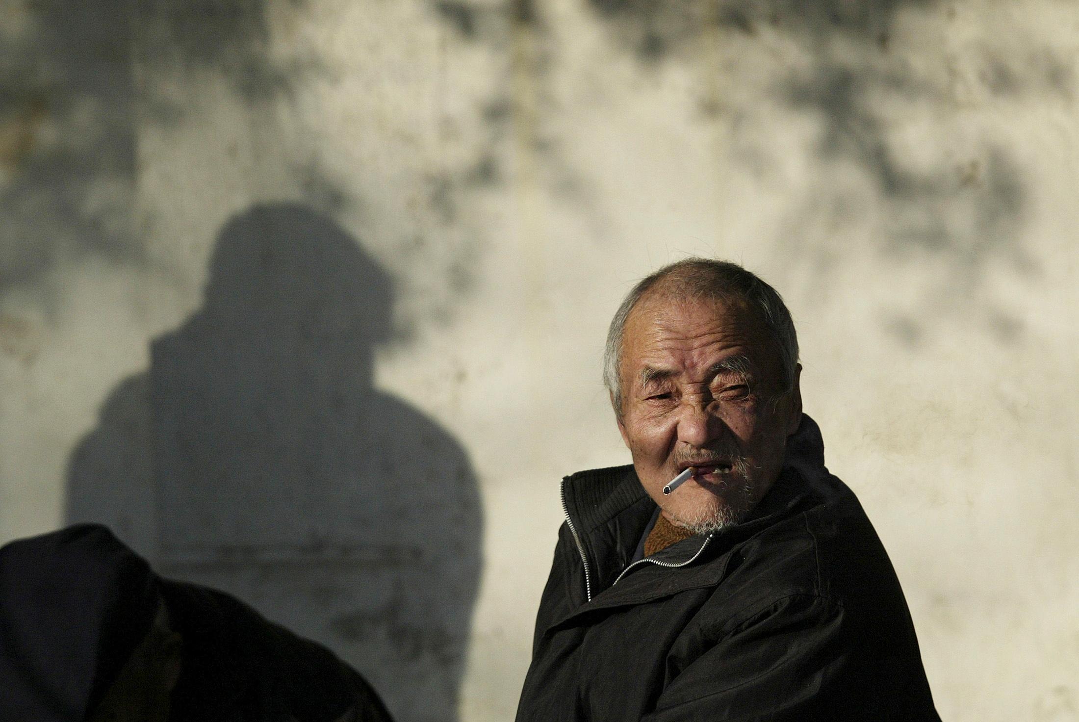 An elderly man smokes on a street in Nanjing, Jiangsu province December 27, 2010. REUTERS/Sean Yong