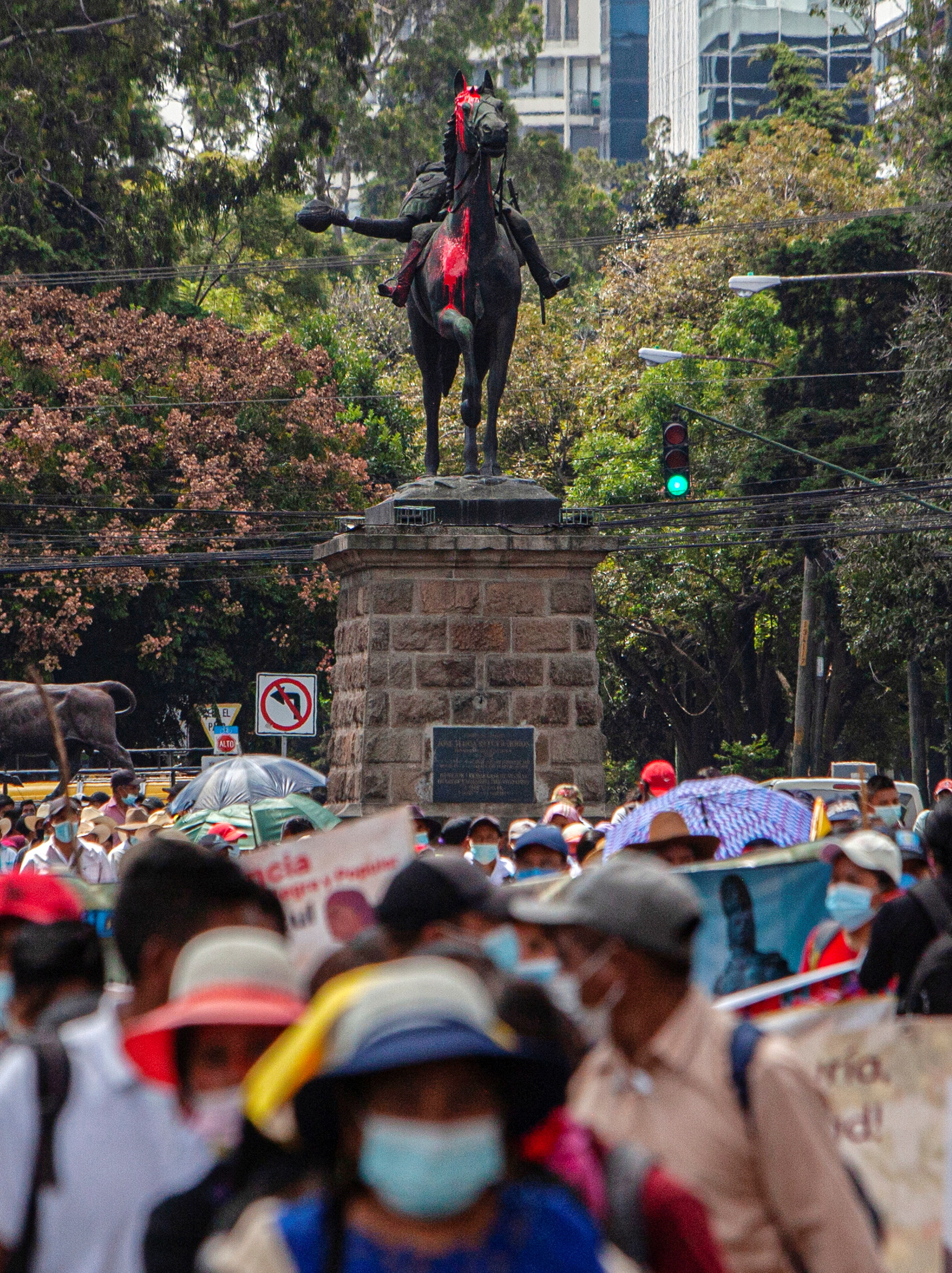 Demonstrators walk past the statue of former President Jose Maria Reina Barrios after people attempted to topple it during protests against the treatment of indigenous people by European conquerors, during Hispanic Heritage Day, in Guatemala City, Guatemala, October 12, 2021. REUTERS/Stringer