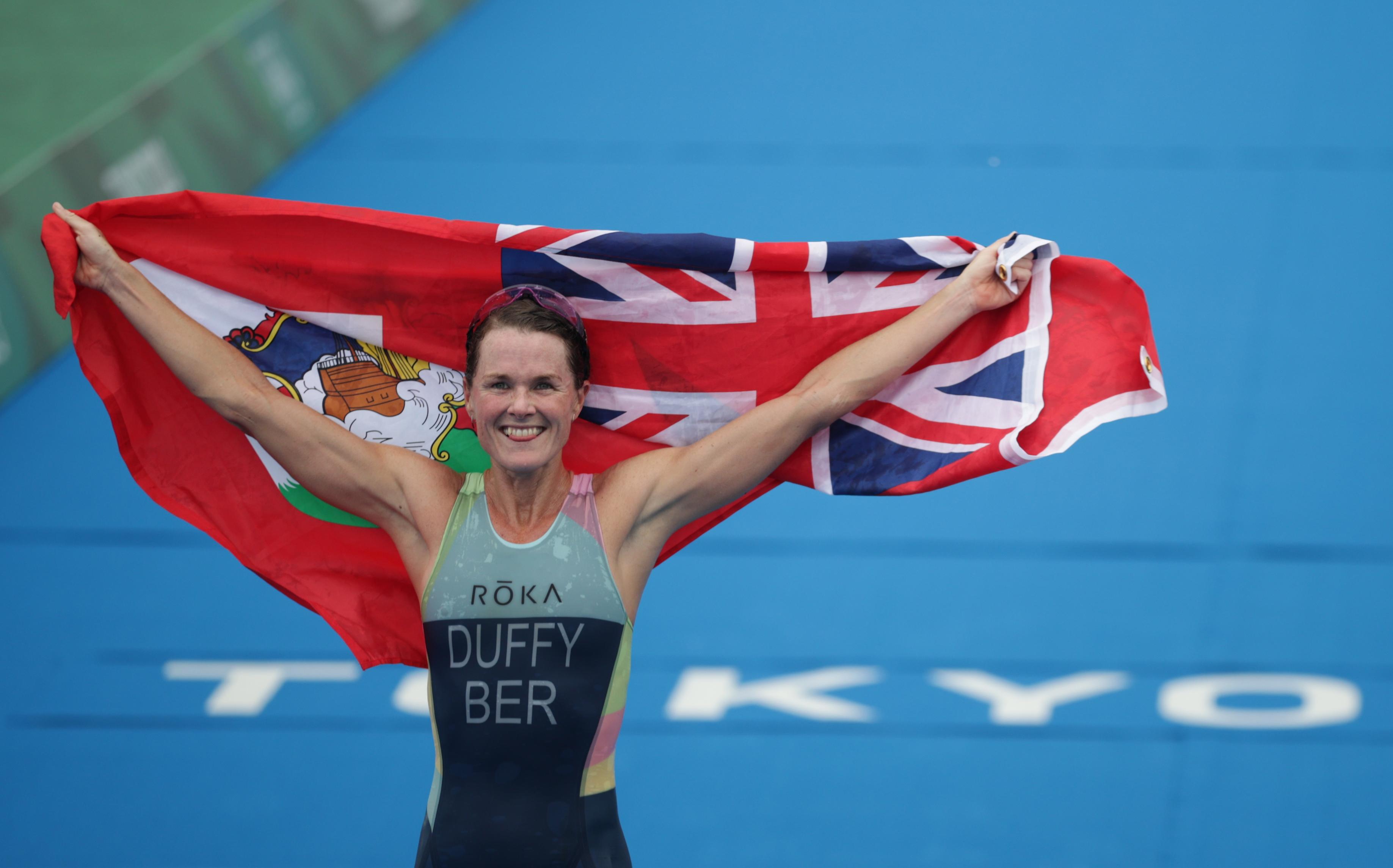 Tokyo 2020 Olympics - Triathlon - Women's Olympic Distance - Final - Odaiba Marine Park, Tokyo, Japan July 27, 2021. Flora Duffy of Bermuda holds national flag as she celebrates victory. REUTERS/Hannah Mckay
