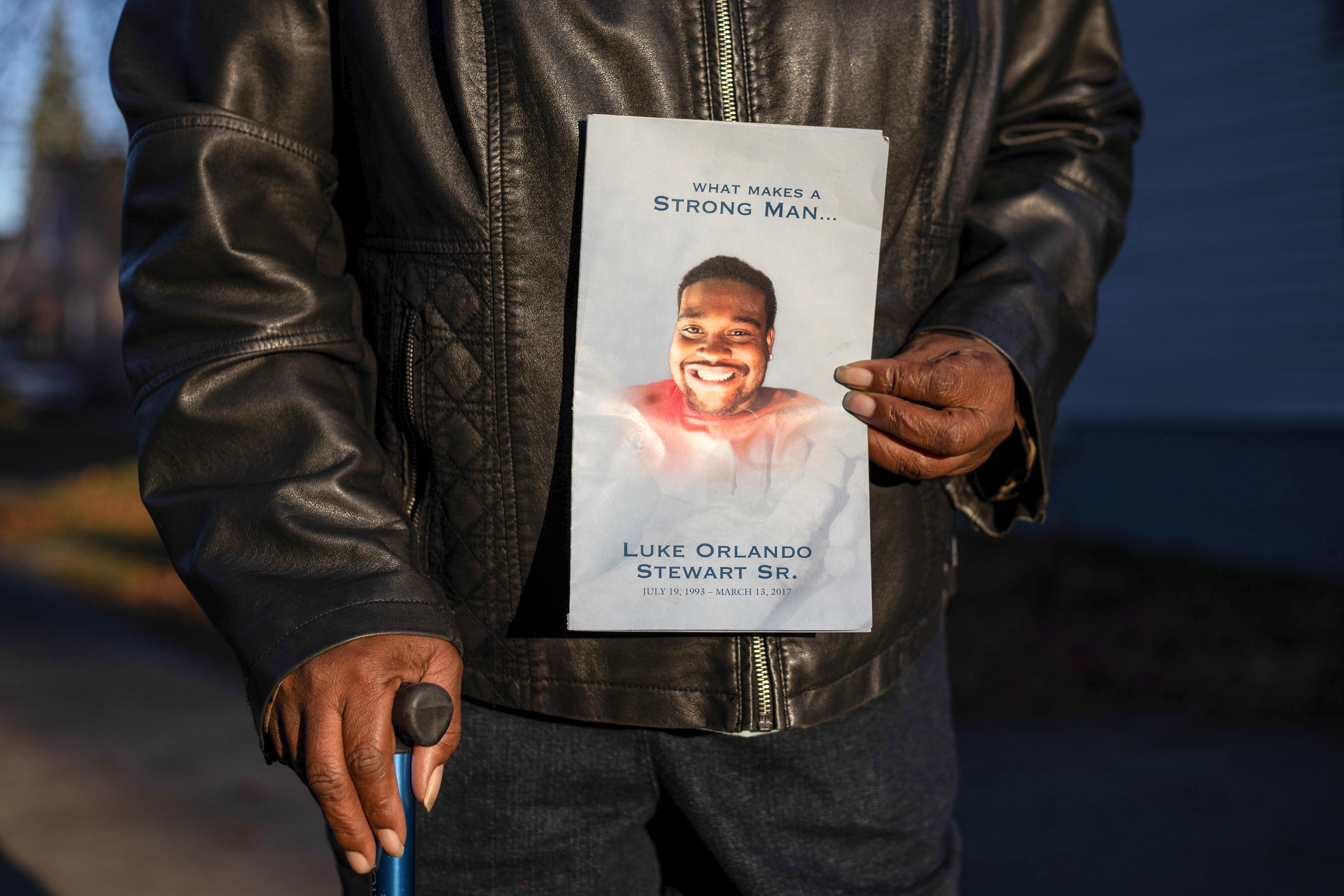 Mary Stewart holds an obituary of her son Luke Stewart, in Cleveland, Ohio, U.S., November 12, 2020. REUTERS/Megan Jelinger