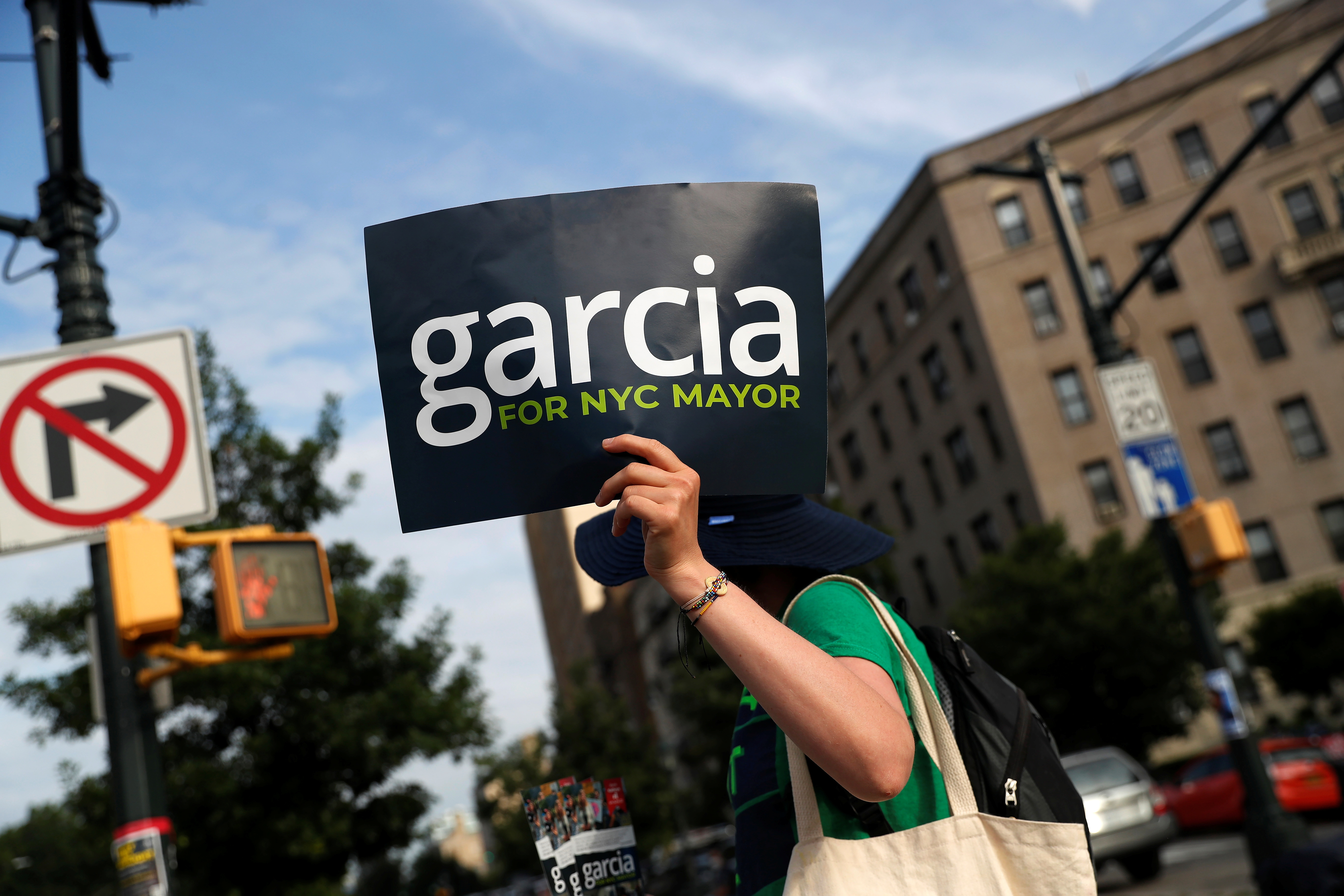 A supporter of Democratic candidate for New York City Mayor Kathryn Garcia holds a sign outside the Brooklyn Museum voting station in New York City, U.S., June 22, 2021. REUTERS/Shannon Stapleton