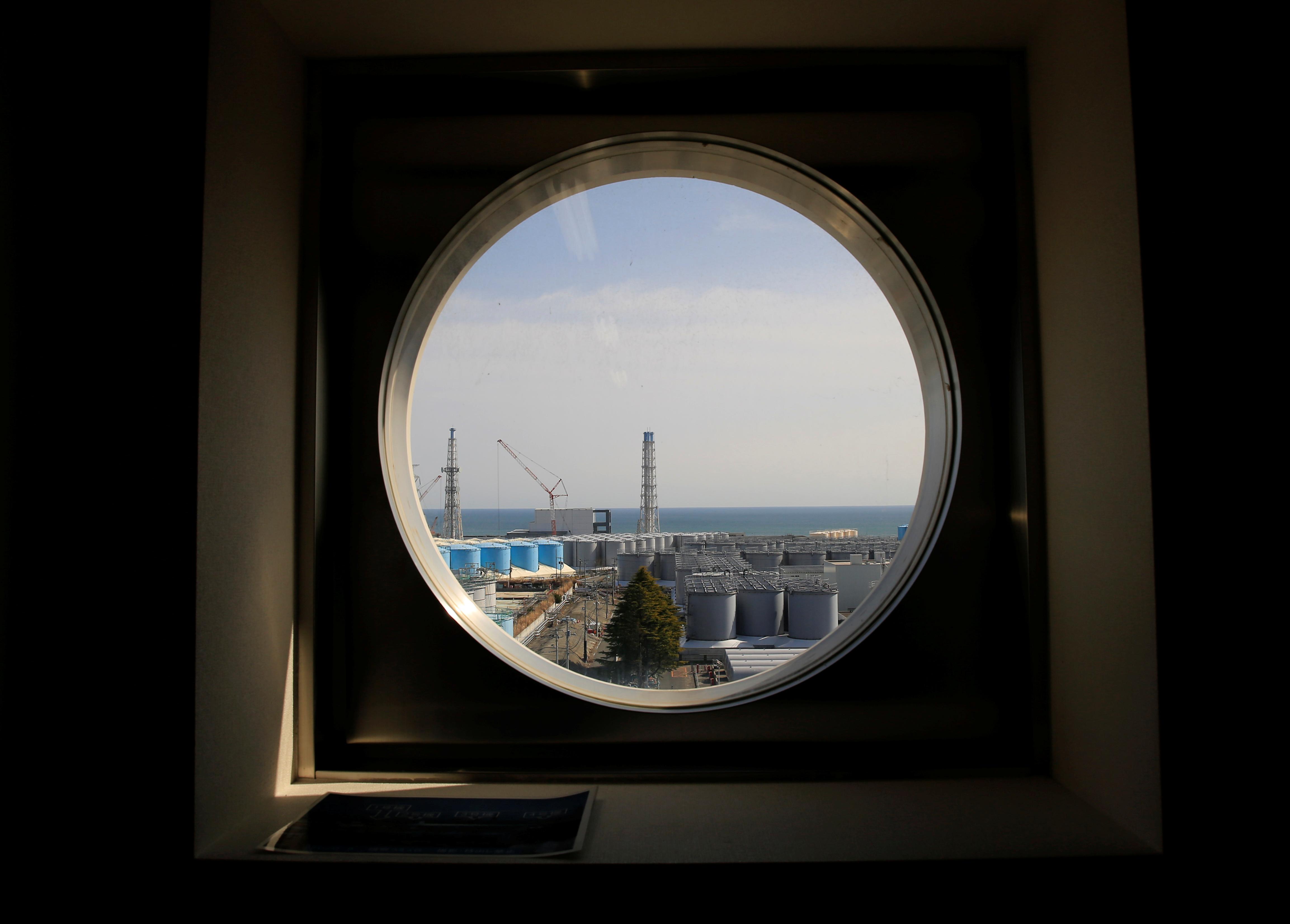 The storage tanks for treated water are seen through a window at the tsunami-crippled Fukushima Daiichi nuclear power plant in Okuma town, Fukushima prefecture, Japan March 1, 2021. REUTERS/Sakura Murakami