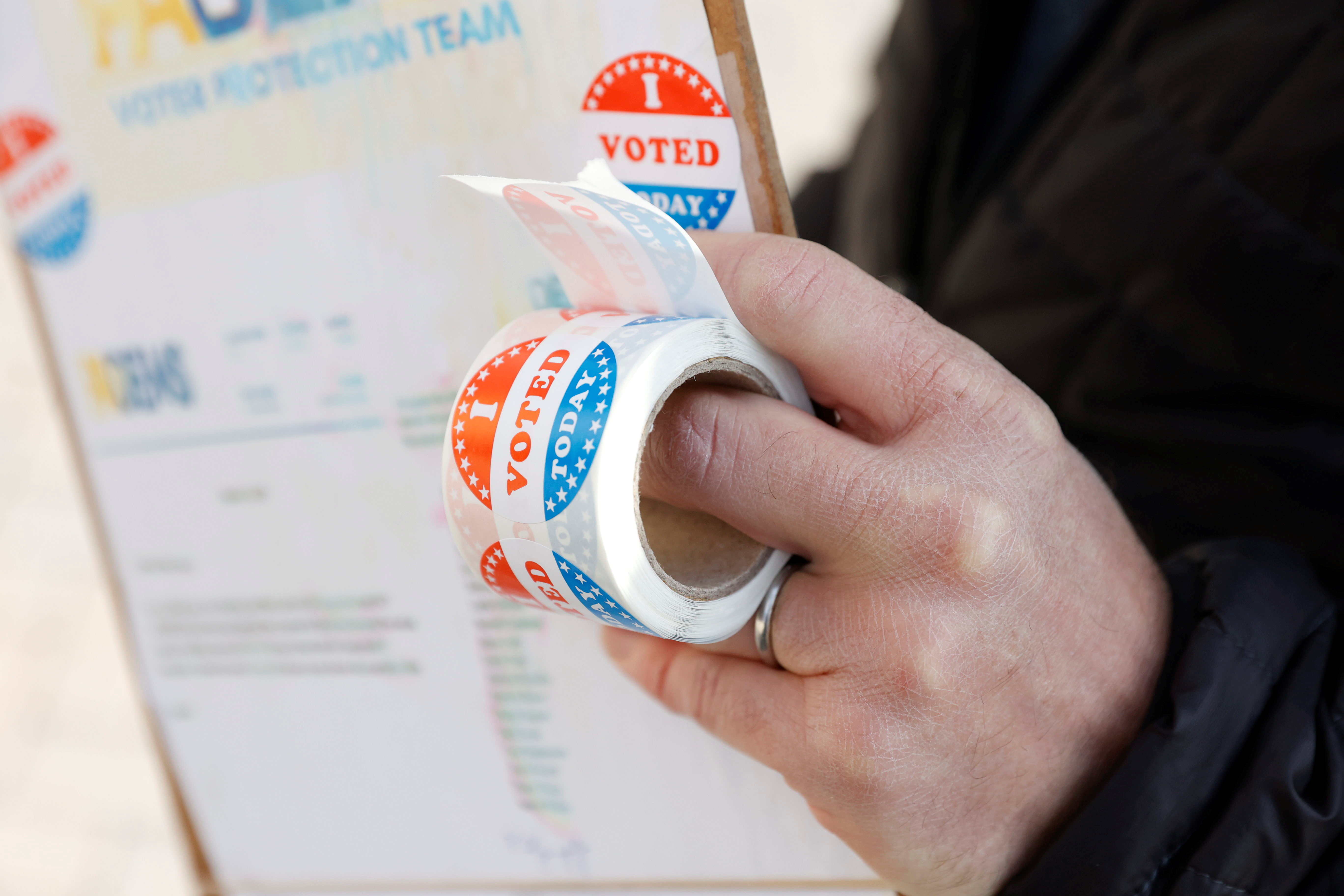 A person holds stickers saying