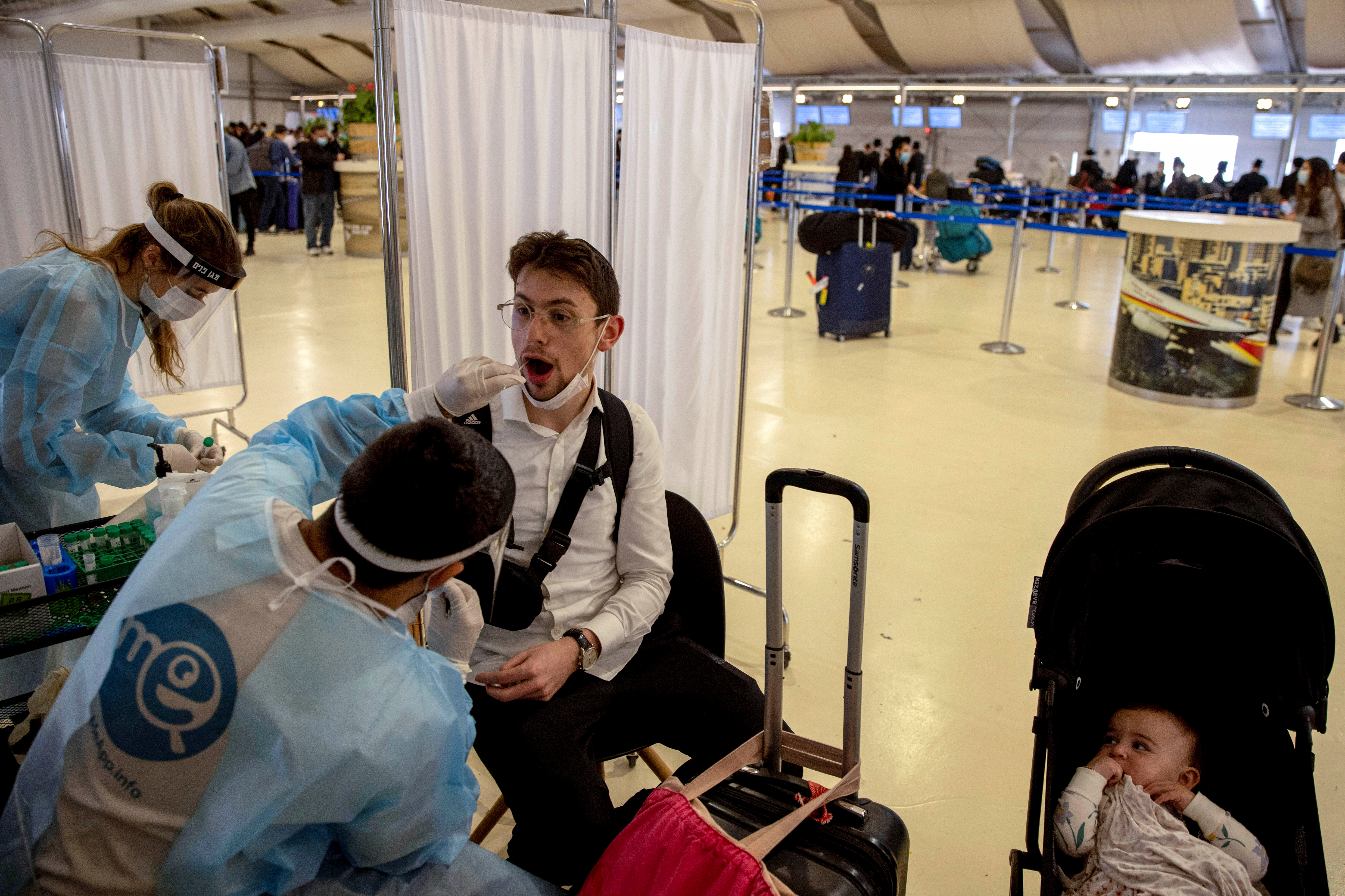 A healthcare worker takes a swab sample from a man for the coronavirus disease (COVID-19) test, after returning from overseas, at Ben Gurion International Airport in Lod, near Tel Aviv, Israel April 13, 2021. REUTERS/Ronen Zvulun.