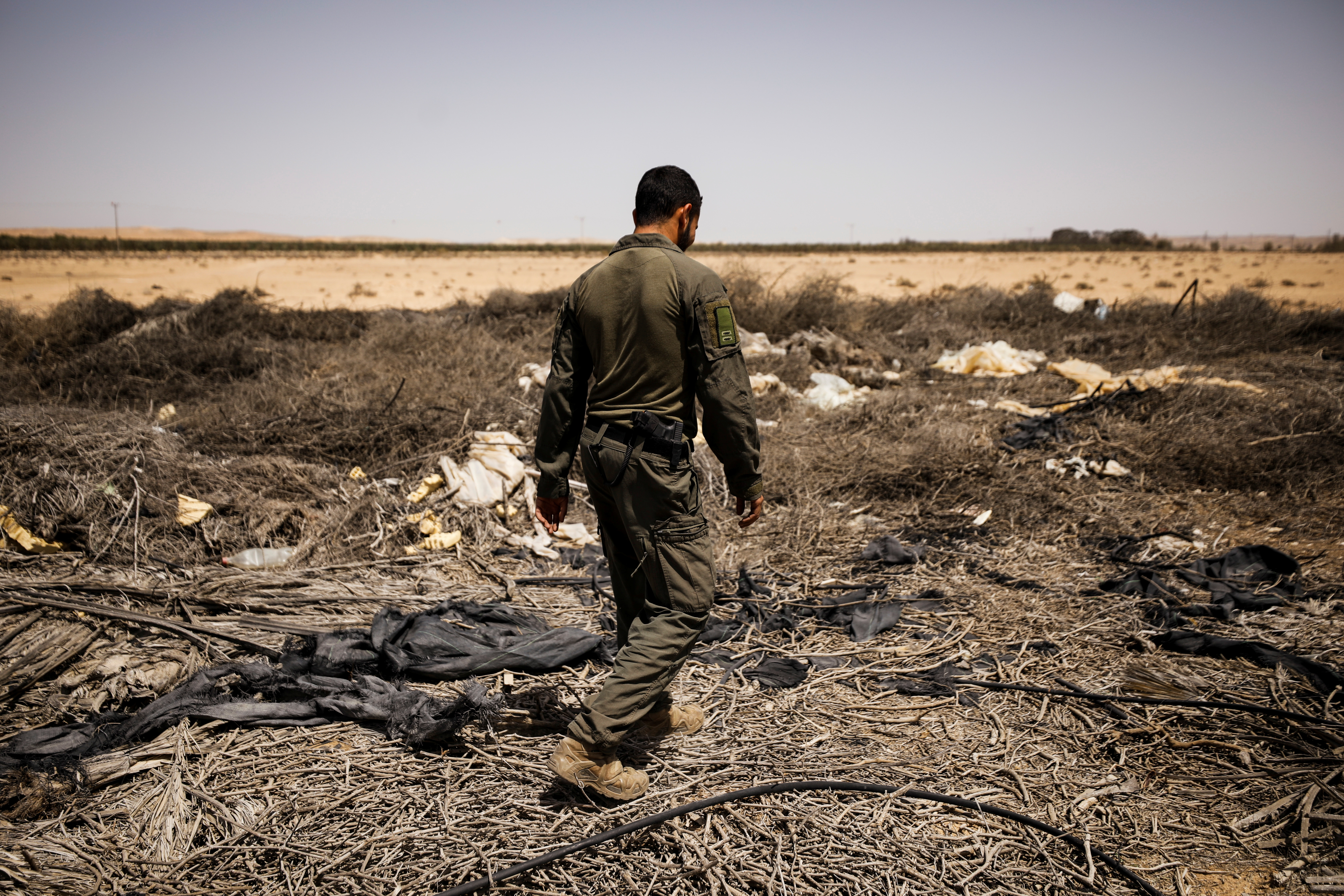 An Israeli soldier surveys the area after a Syrian missile exploded in southern Israel, the Israeli military said, near Ashalim, southern Israel April 22, 2021. REUTERS/Amir Cohen