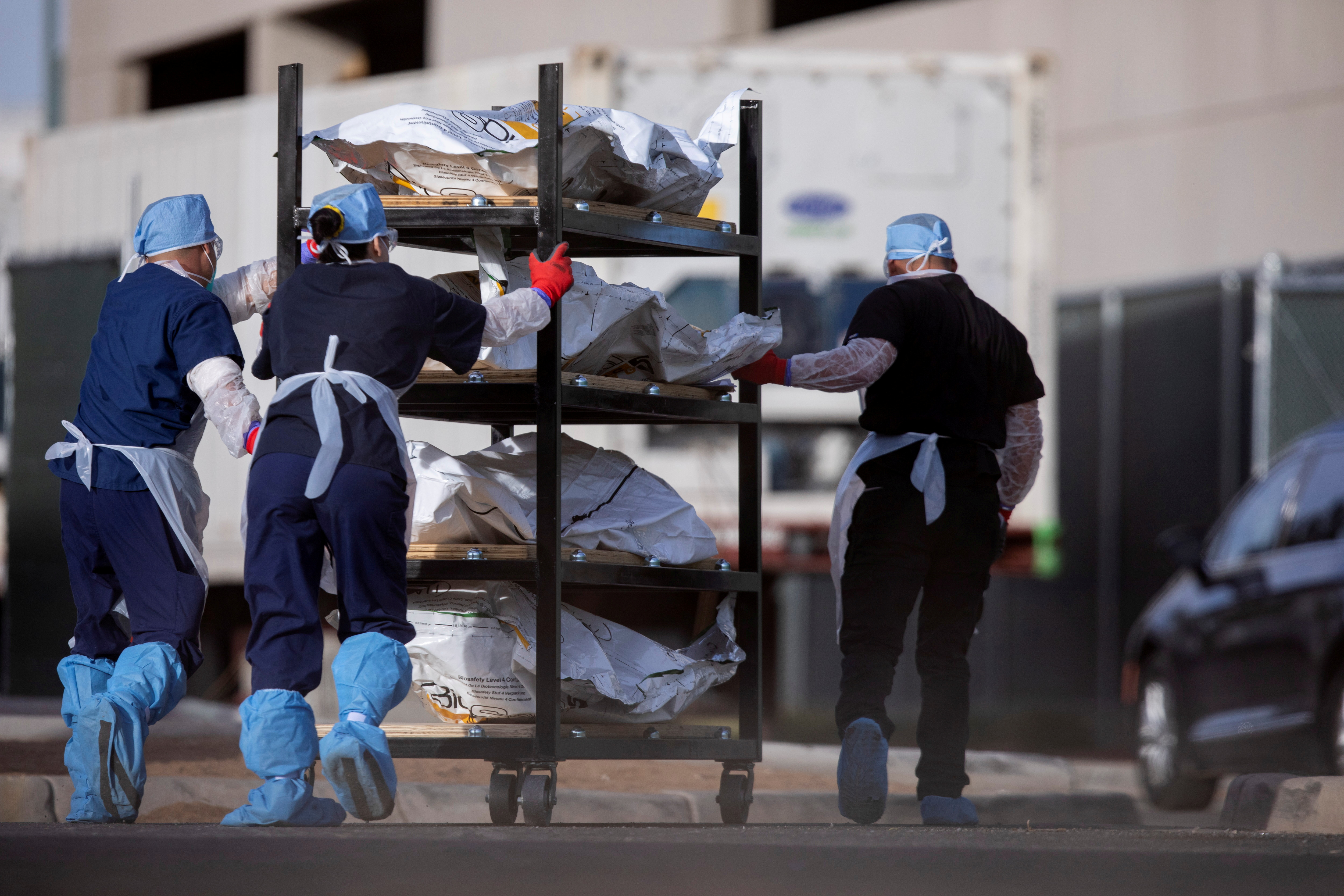 El Paso County Medical Examiner's Office staff roll bodies that are in bags labeled