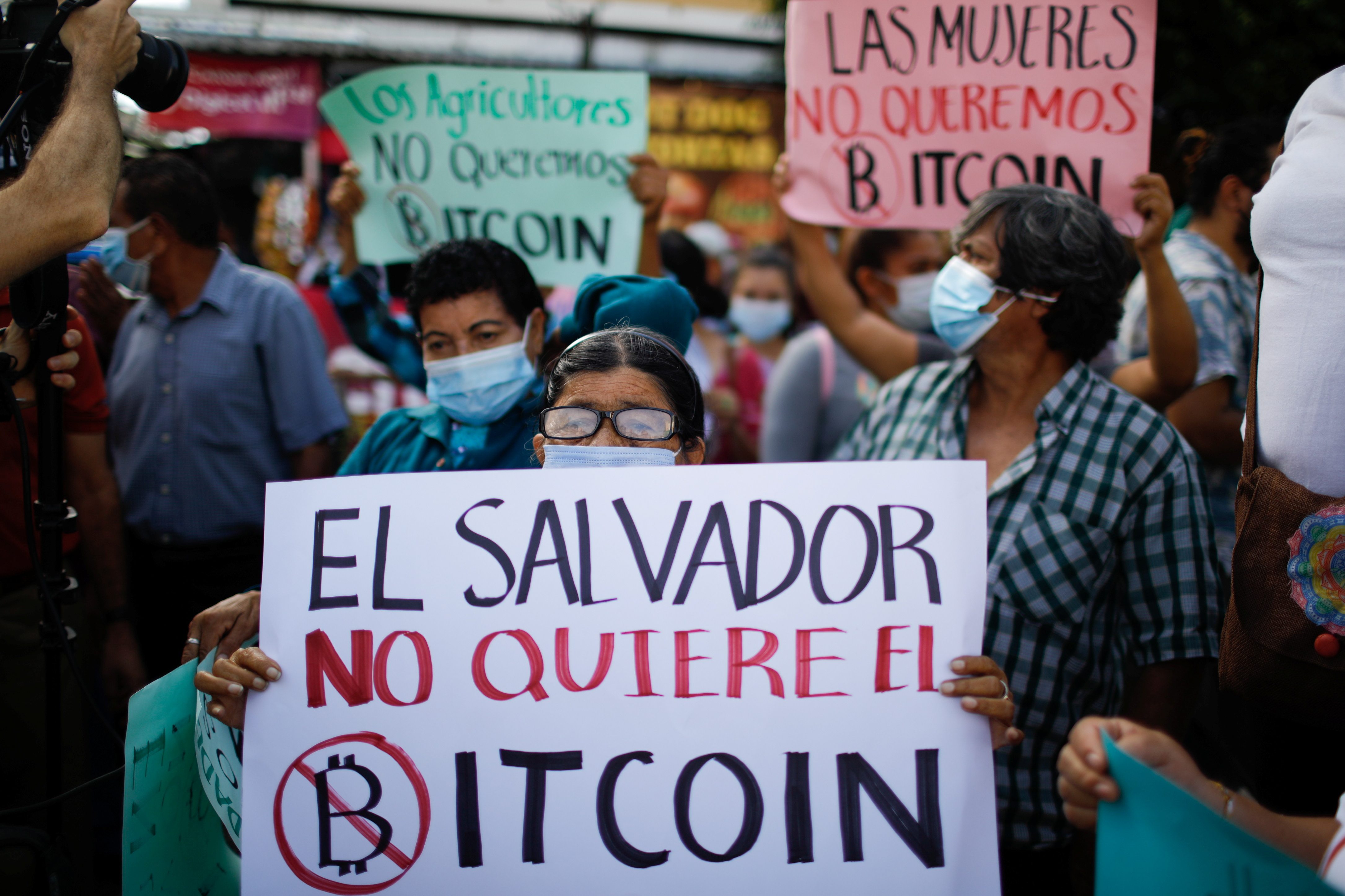 A person holds a sign that reads 'El Salvador doesn't want Bitcoin' as people participate in a protest against the use of Bitcoin as legal tender, in San Salvador, El Salvador, September 7, 2021. REUTERS/Jose Cabezas