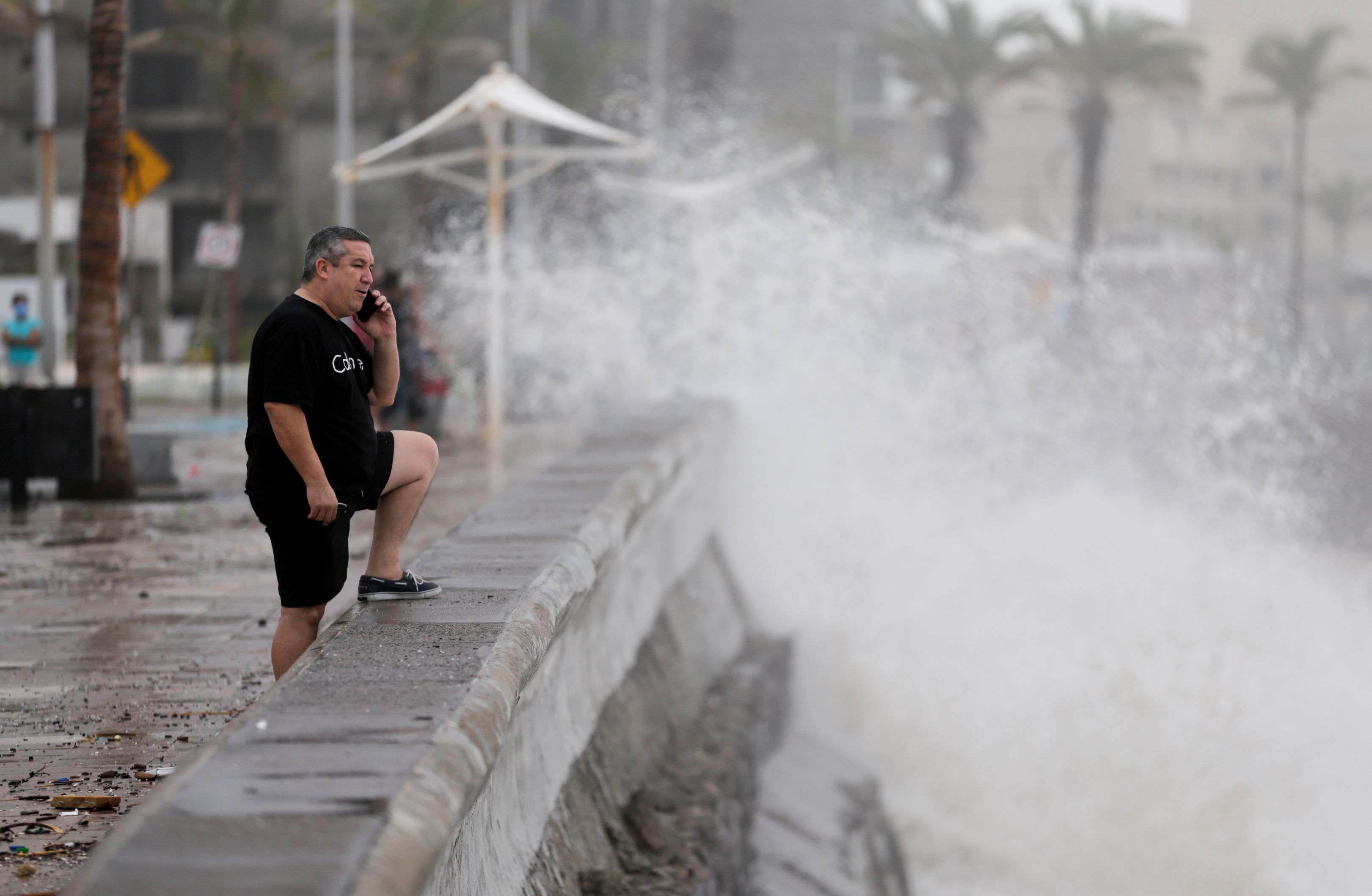A man speaks on his mobile phone as hurricane Pamela pounds the Pacific coast resort with strong winds as it makes landfall in Mazatlan, Mexico October 13, 2021. REUTERS/Daniel Becerril