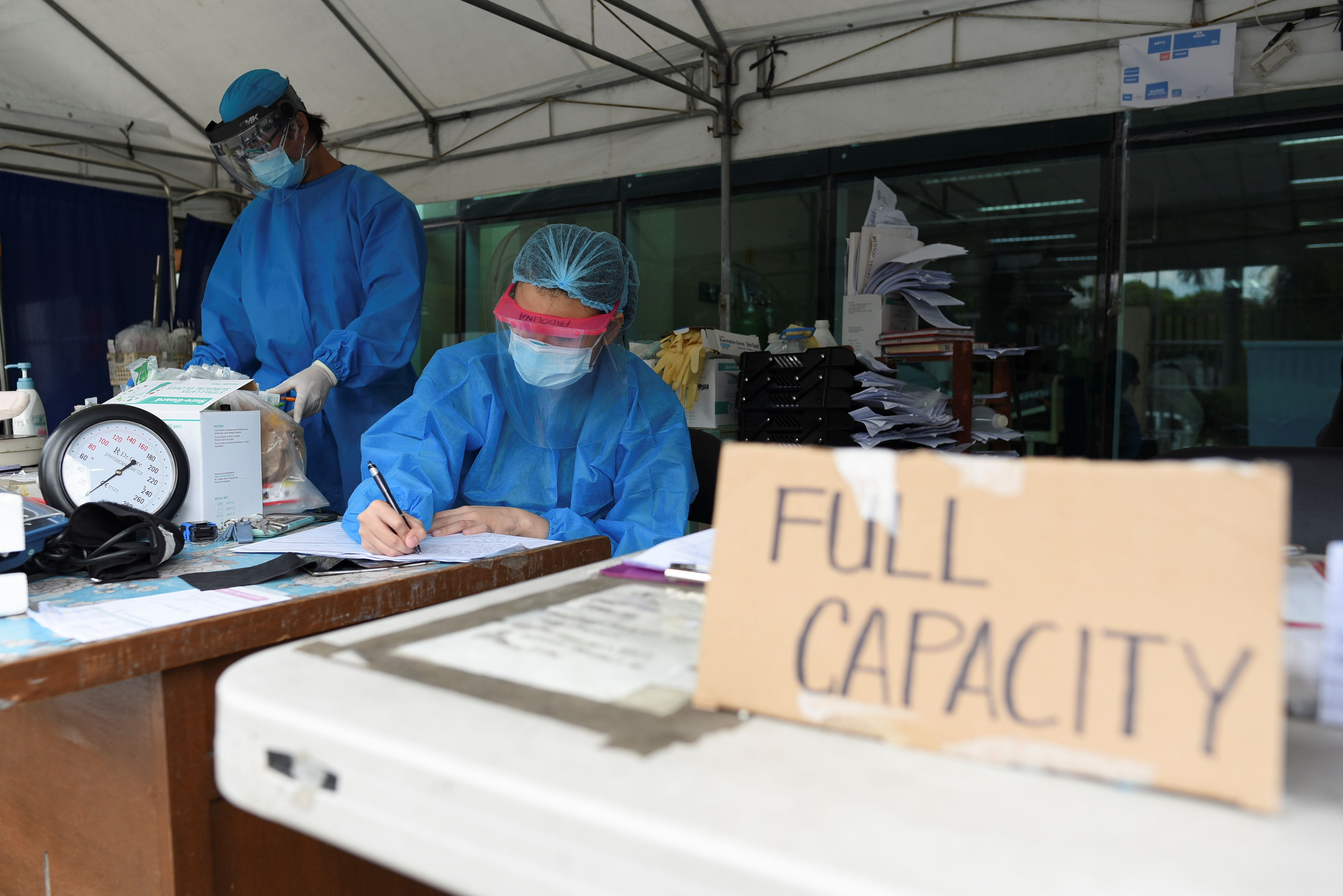 Health workers sort patients' files at a triage area in Santa Ana Hospital, where a sign indicating that the hospital's coronavirus disease (COVID-19) facility is at full capacity is displayed, in Manila, Philippines, April 9, 2021. REUTERS/Lisa Marie David