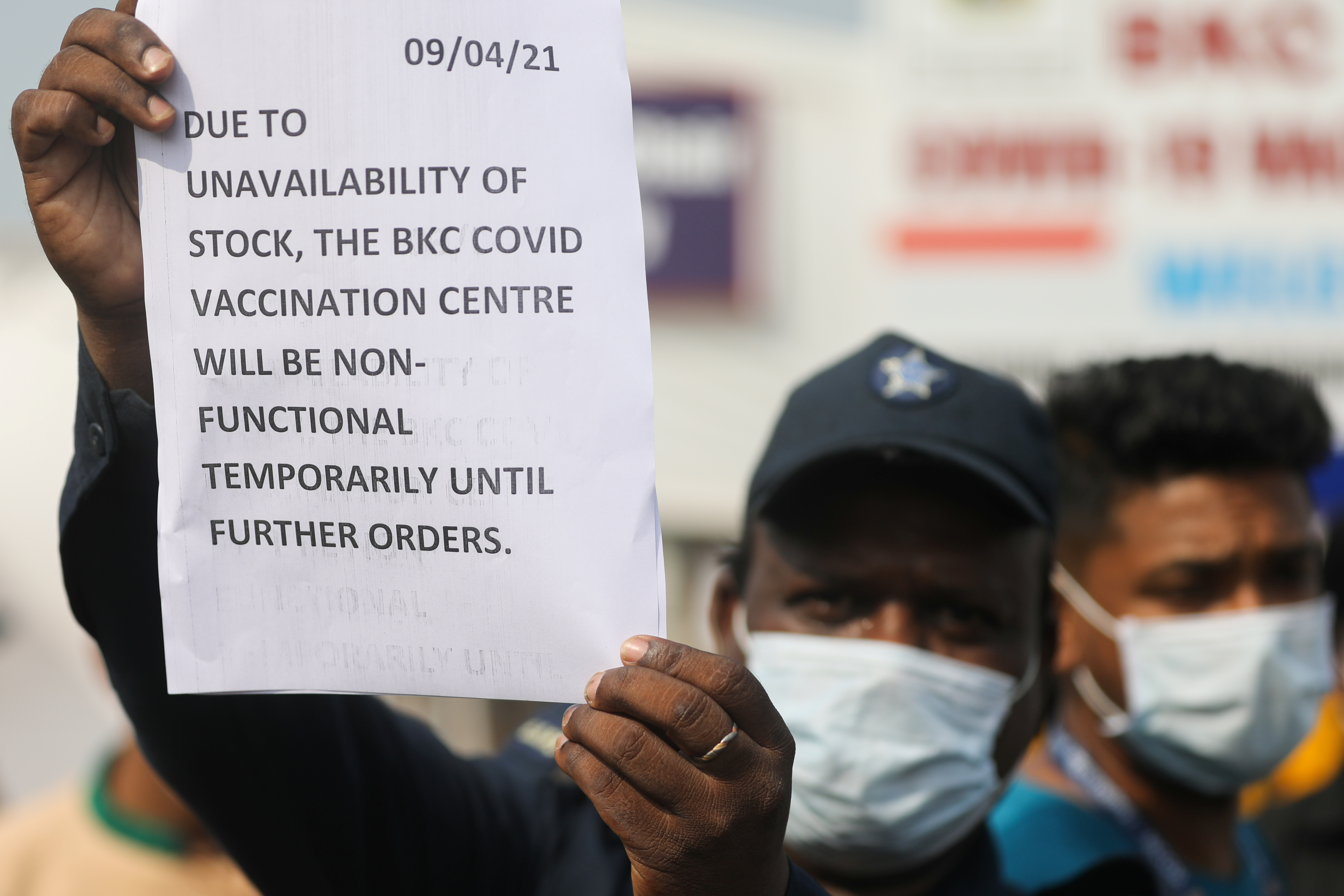 A guard holds up a notice to inform people about the shortage of coronavirus disease (COVID-19) vaccine supplies at a vaccination centre, in Mumbai, India, April 9, 2021. REUTERS/Francis Mascarenhas