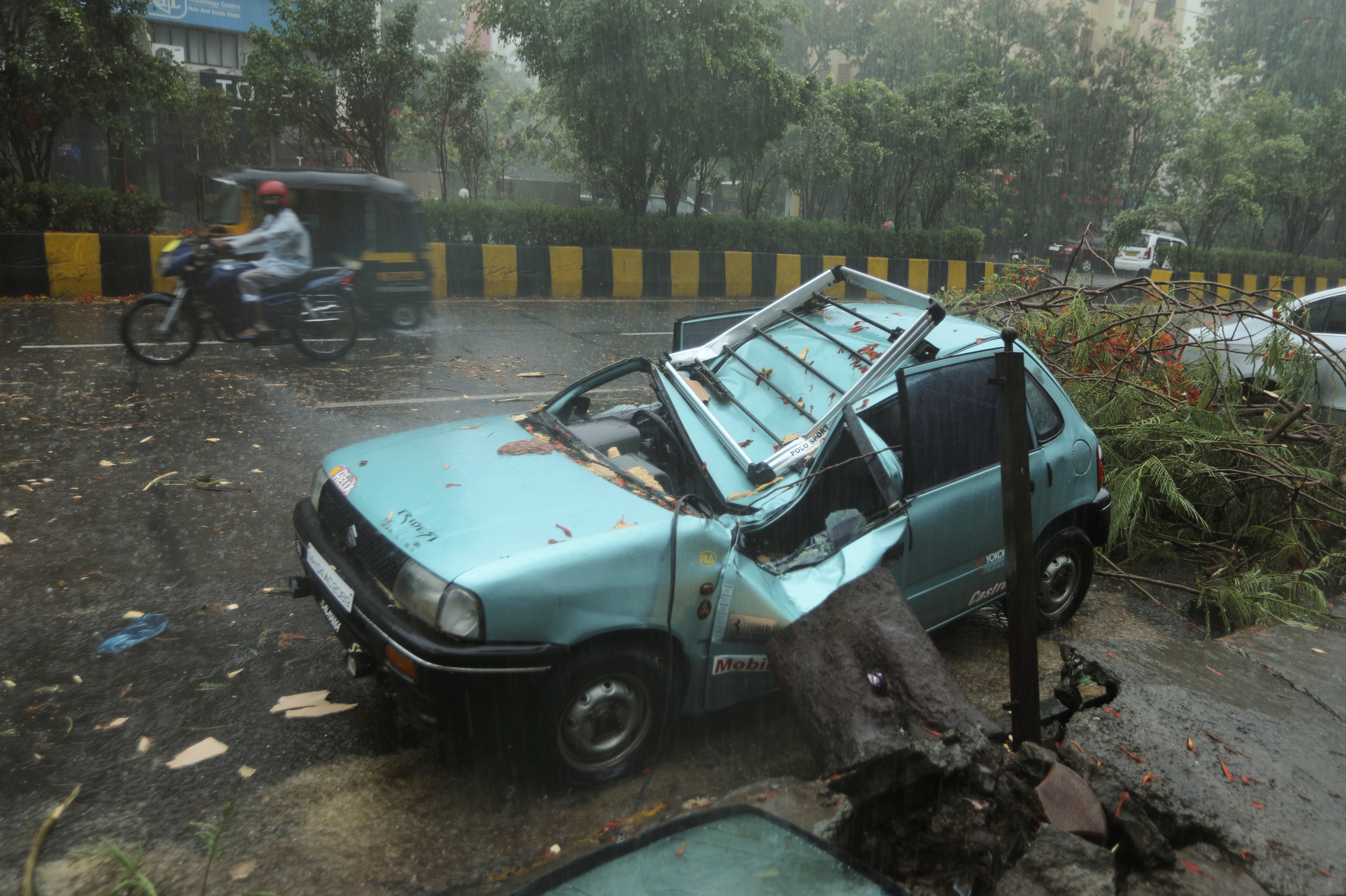 A damaged car is seen on a road after a tree fell on it due to strong winds caused by Cyclone Tauktae in Mumbai, India, May 17, 2021. REUTERS/Francis Mascarenhas