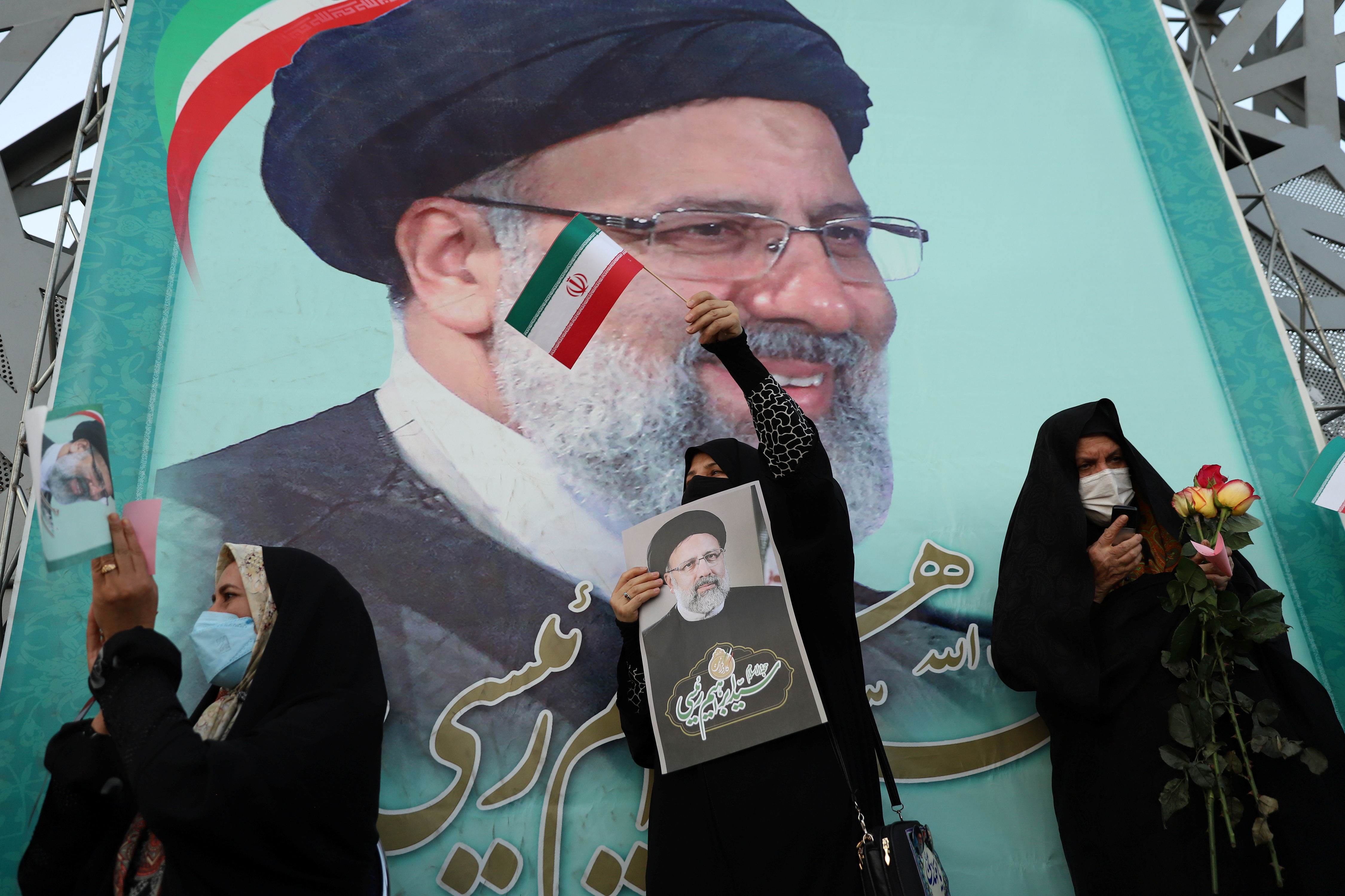 A supporter of Ebrahim Raisi displays his portrait during a celebratory rally for his presidential election victory in Tehran, Iran June 19, 2021. Majid Asgaripour/WANA (West Asia News Agency) via REUTERS