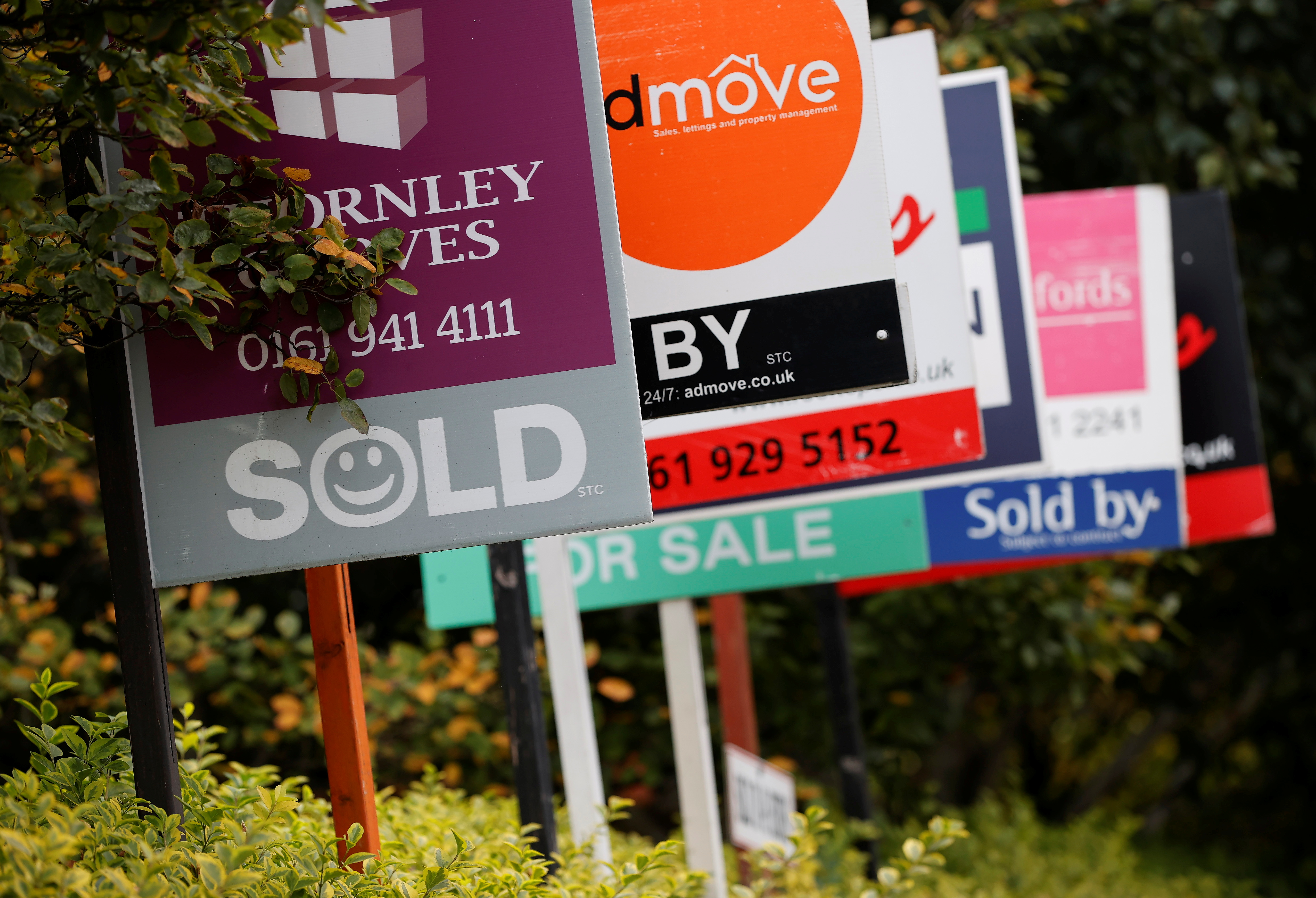 Estate Agent's boards are lined up outside a housing development in Manchester, Britain, August 31, 2021. REUTERS/Phil Noble
