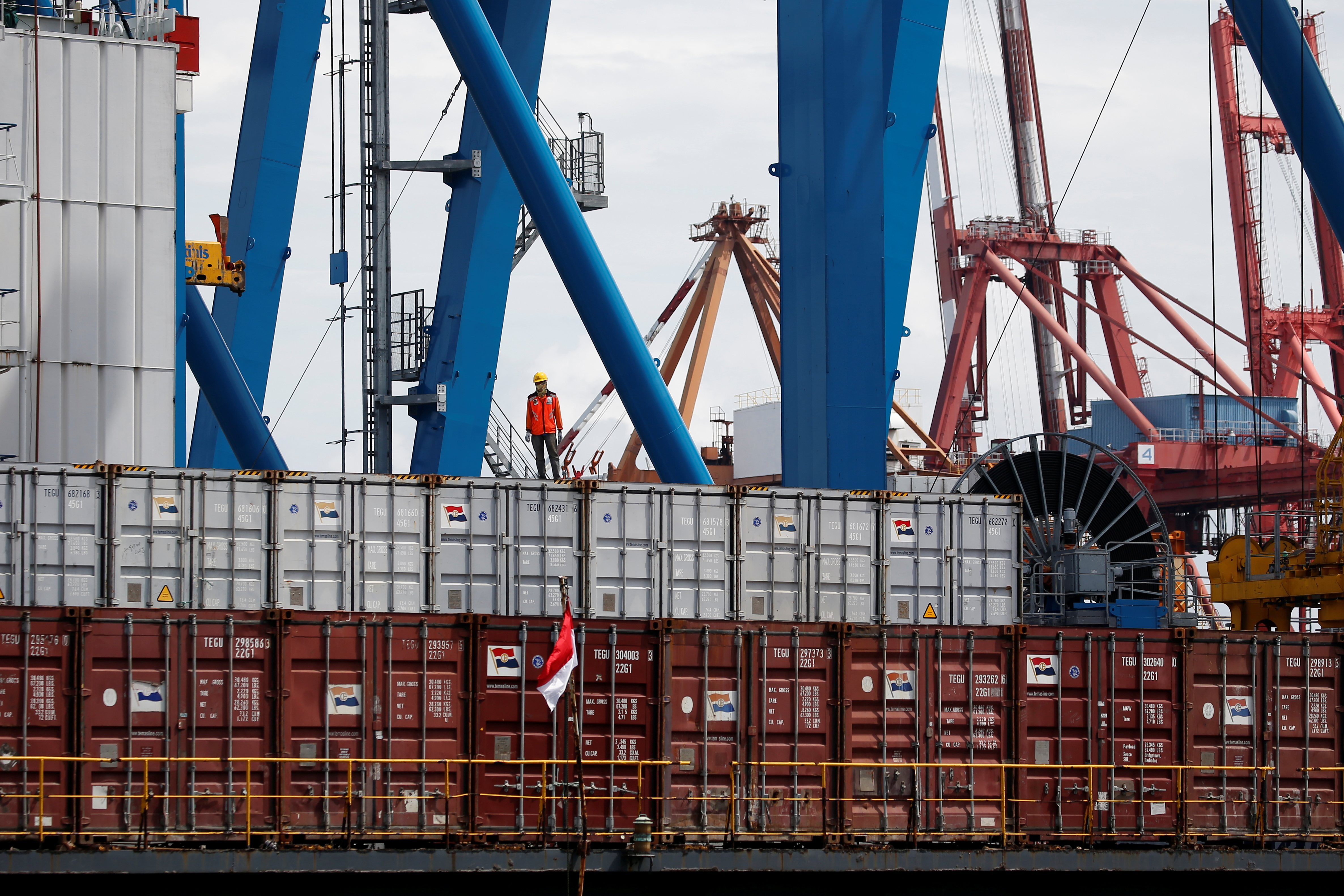 A worker stands on a container at Tanjung Priok Port in Jakarta, Indonesia, January 11, 2021. Picture taken January 11, 2021. REUTERS/Willy Kurniawan