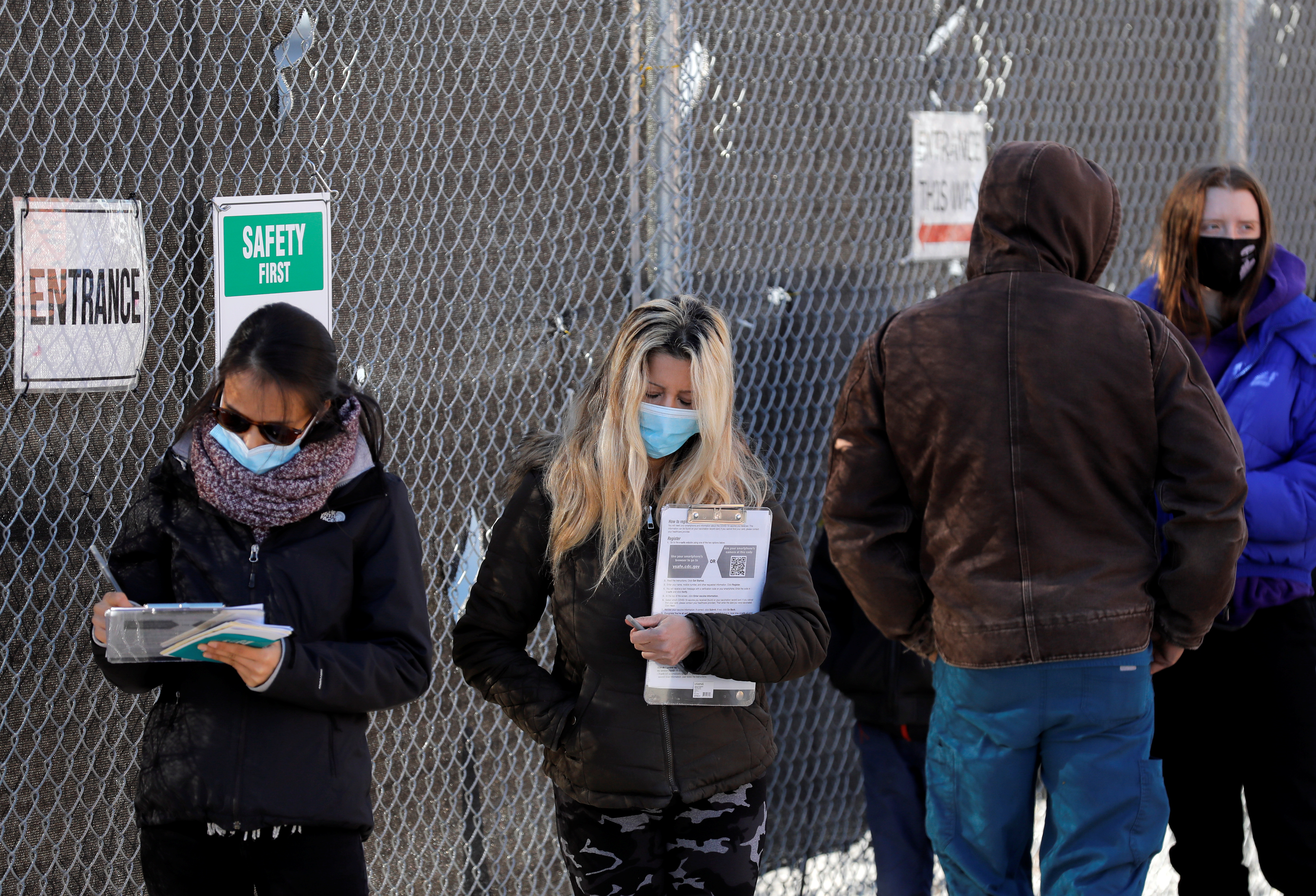 People line up to receive a dose of the coronavirus disease (COVID-19) vaccine at a mass vaccination site at Brooklyn Army Terminal in New York City, New York, U.S., January 10, 2021. REUTERS/Andrew Kelly
