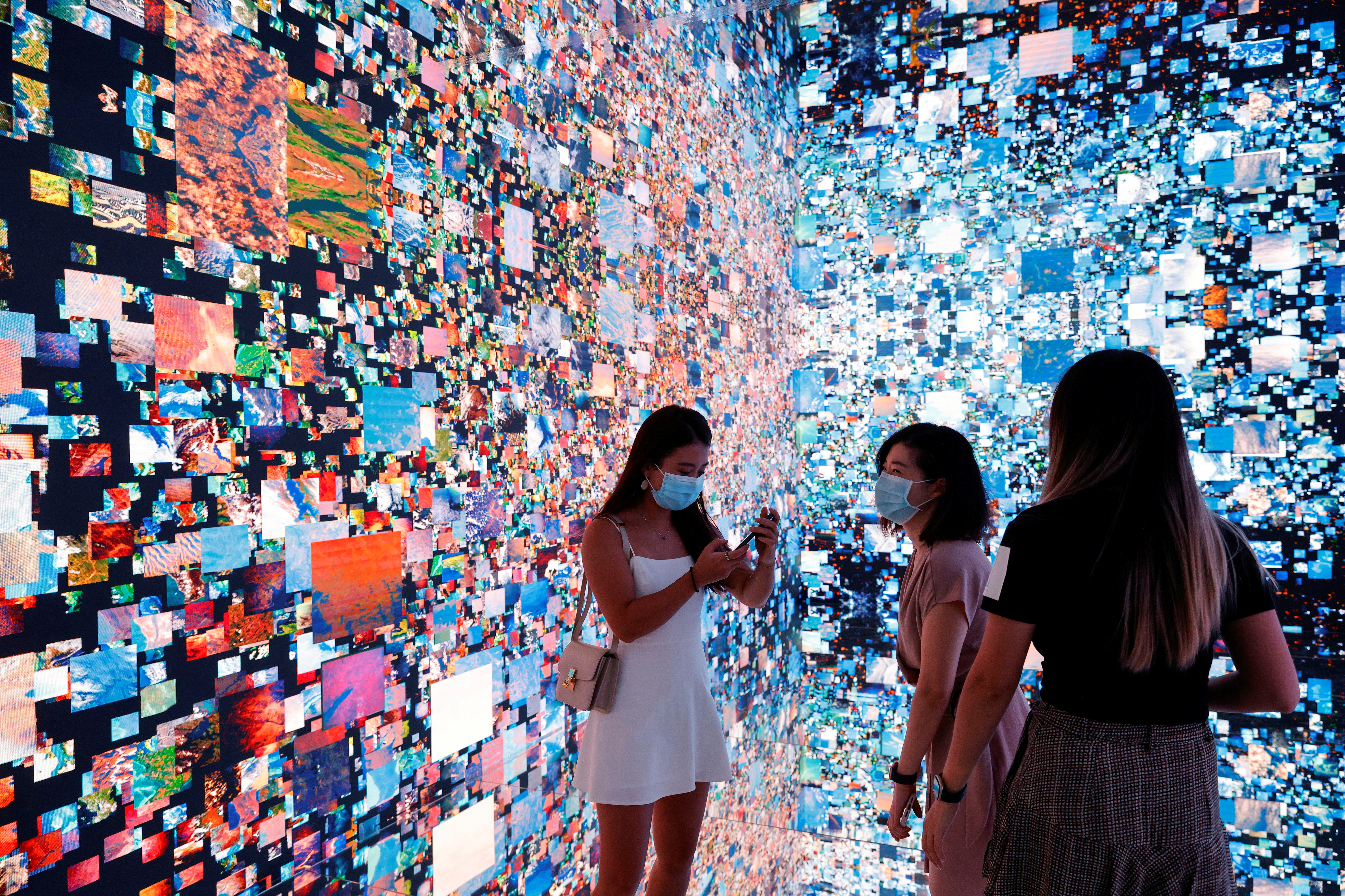 Visitors are pictured in front of an immersive art installation titled