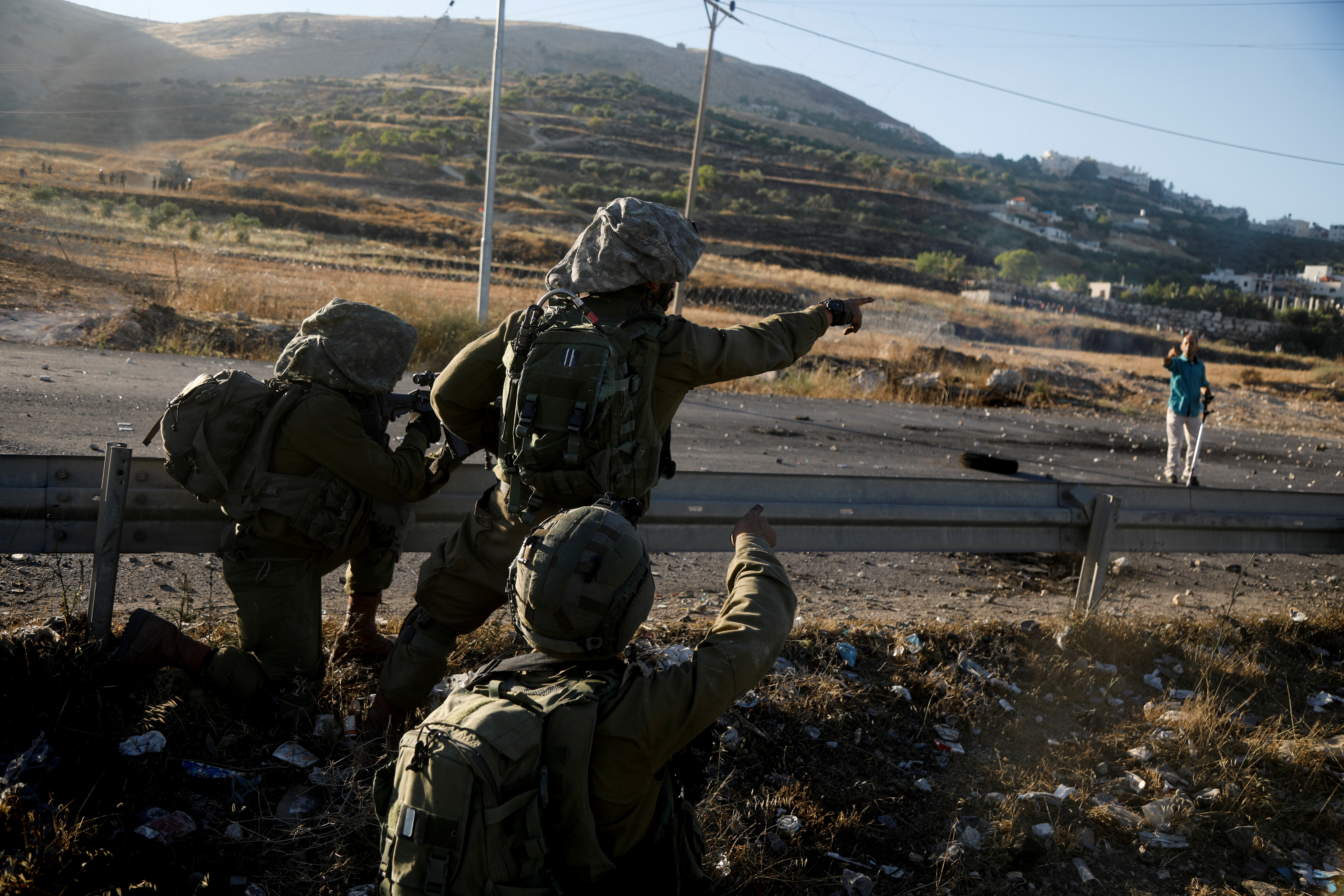 Israel's soldiers talk to a Palestine during an anti-Israel protest over cross-border violence between Palestinian militants in Gaza and the Israeli military, near Hawara checkpoint near Nablus in the Israeli-occupied West Bank, May 18, 2021. REUTERS/Raneen Sawafta