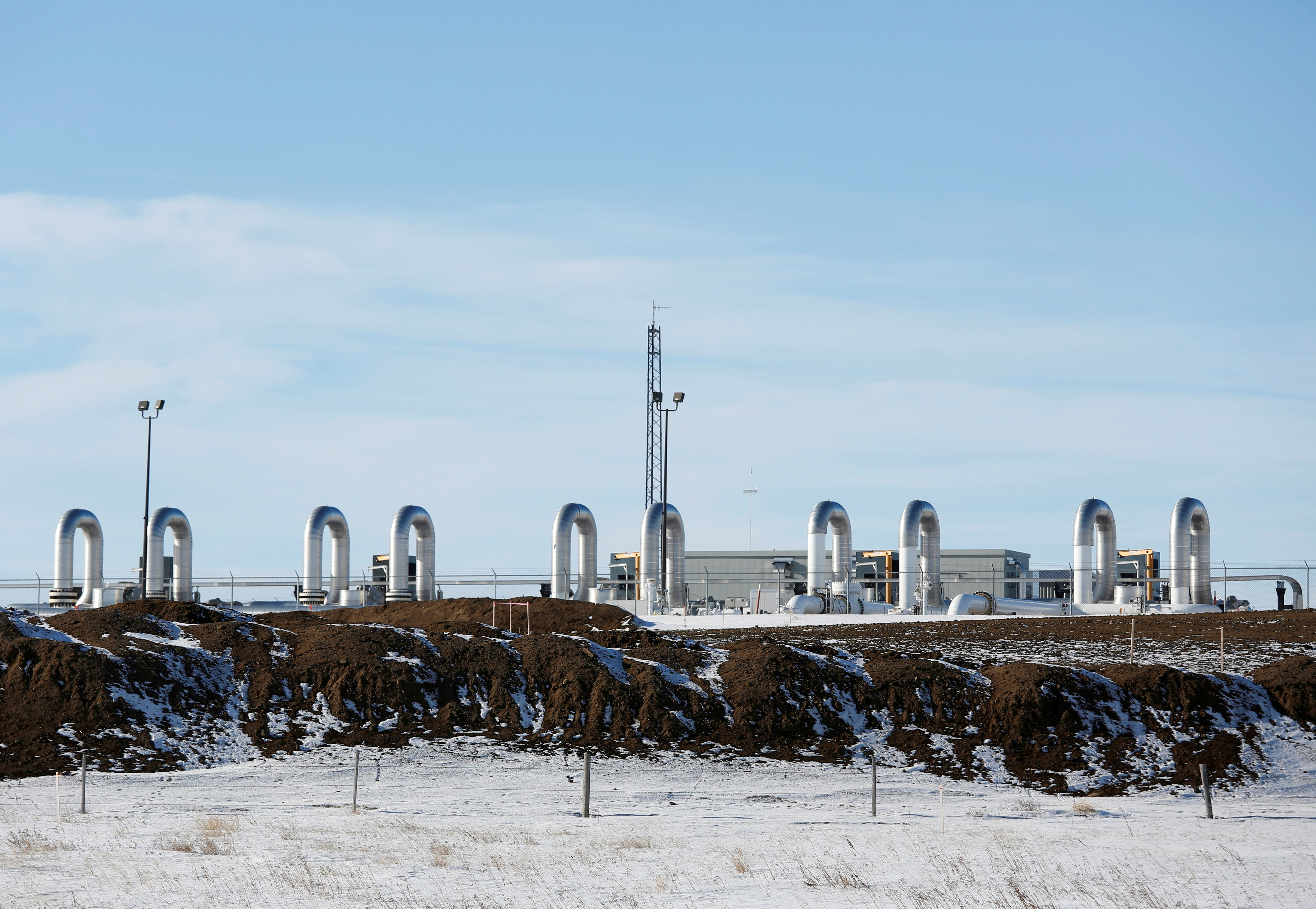A TC Energy pump station sits behind mounds of dirt from the Keystone XL crude oil pipeline as it lies idle near Oyen, Alberta, Canada February 1, 2021.  REUTERS/Todd Korol