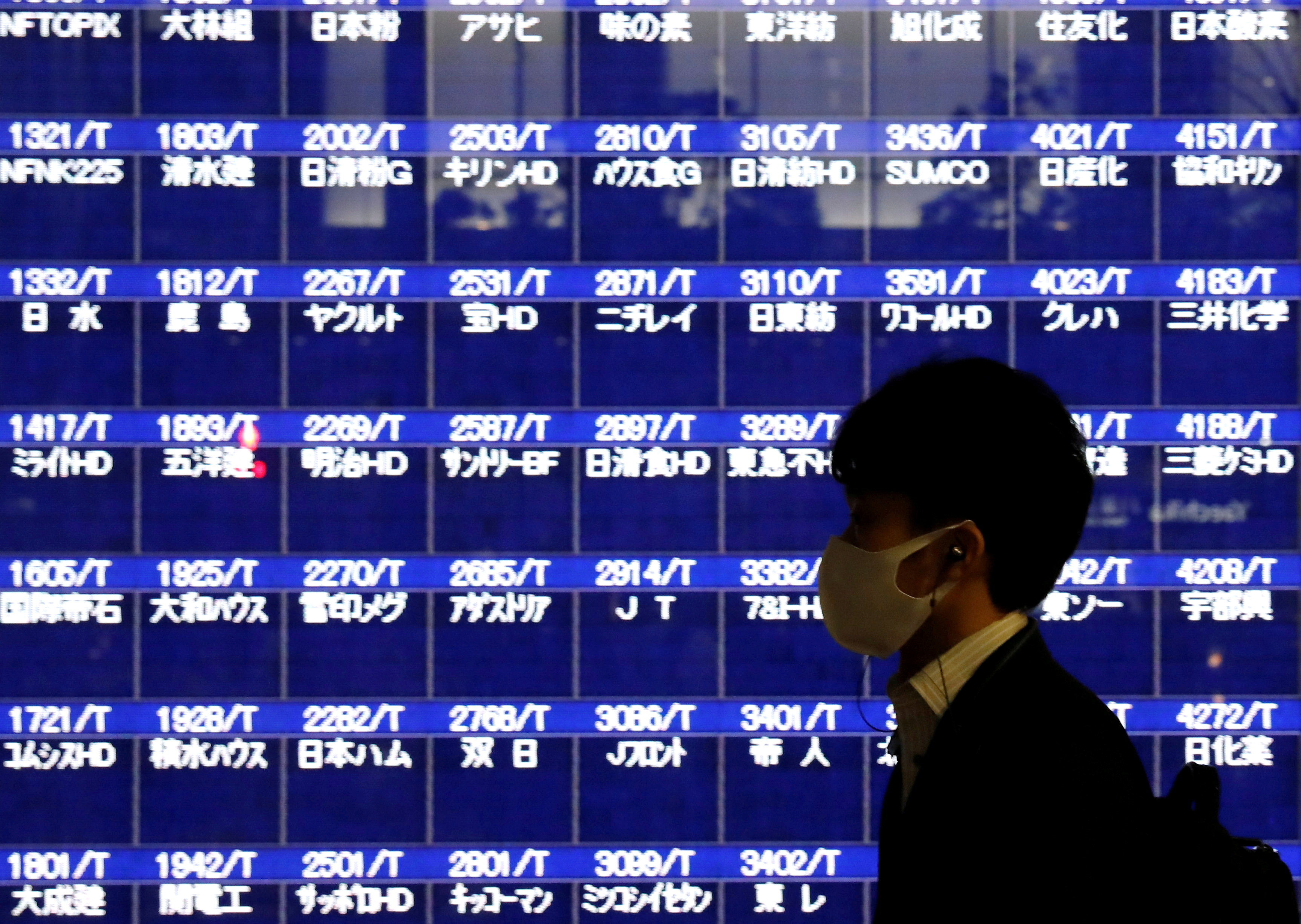 A passerby wearing a protective mask is silhouetted in front of a screen of blank prices on a stock quotation board after Tokyo Stock Exchange temporarily suspended all trading due to system problems, amid the coronavirus disease (COVID-19) pandemic, in Tokyo, Japan October 1, 2020.  REUTERS/Issei Kato/File Photo
