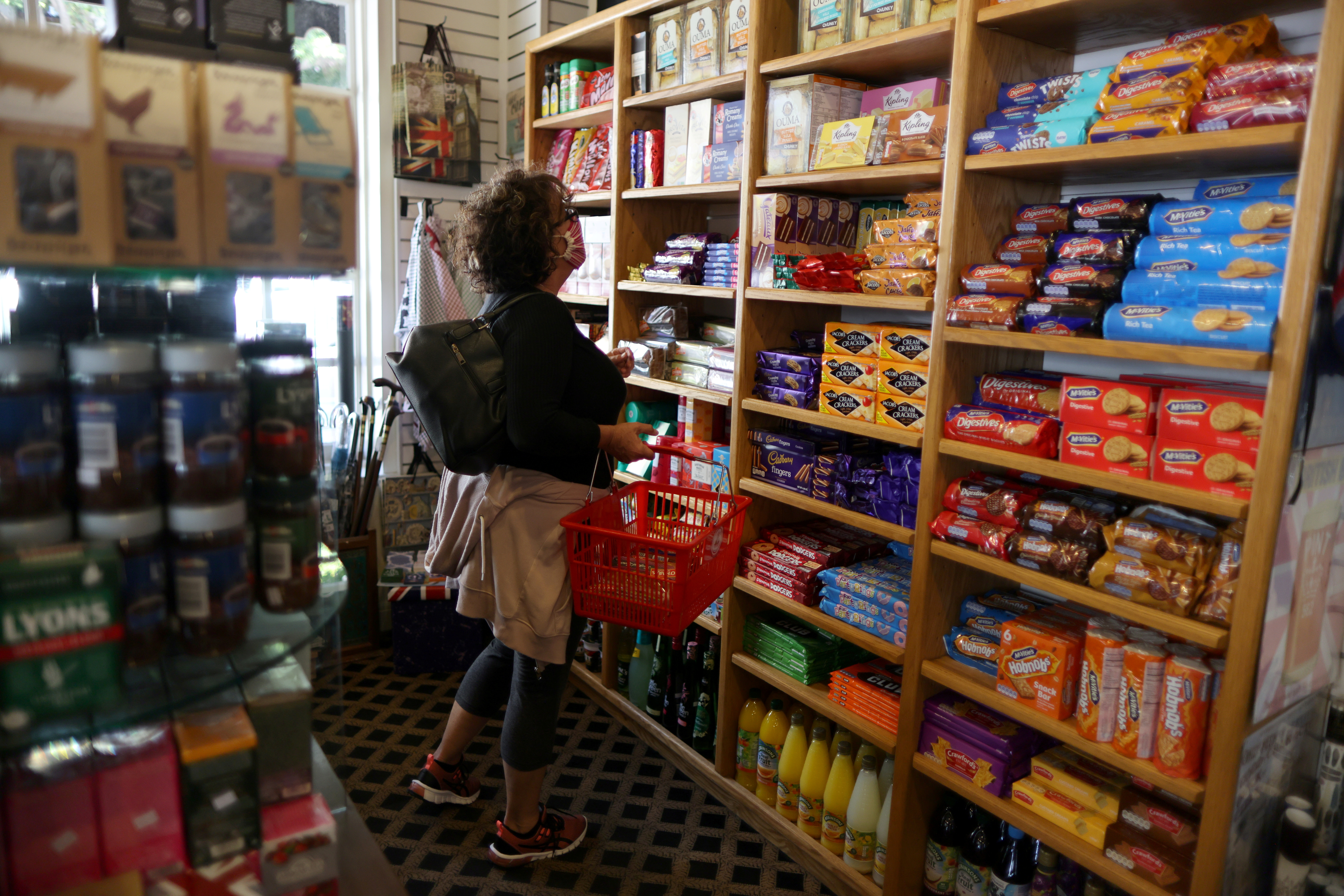 Paula Jarvis, 61, buys biscuits at the King's Head pub as Los Angeles County moves into the least restrictive yellow coronavirus disease (COVID-19) disease reopening tier, in Santa Monica, California, U.S., May 6, 2021. REUTERS/Lucy Nicholson/Files