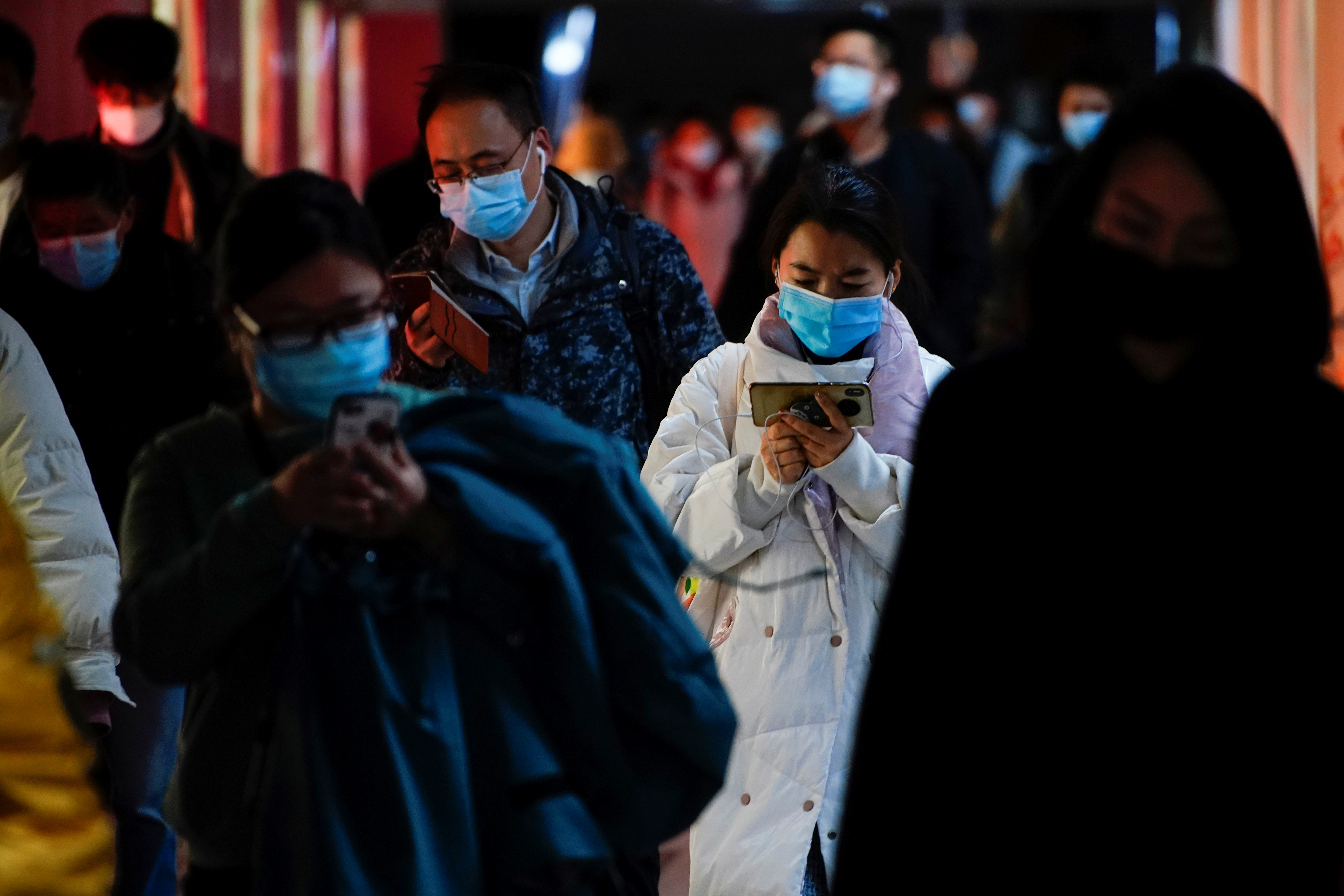 People wearing face masks use their cellphones at a subway station following the coronavirus disease (COVID-19) outbreak, in Shanghai, China January 25, 2021. REUTERS/Aly Song