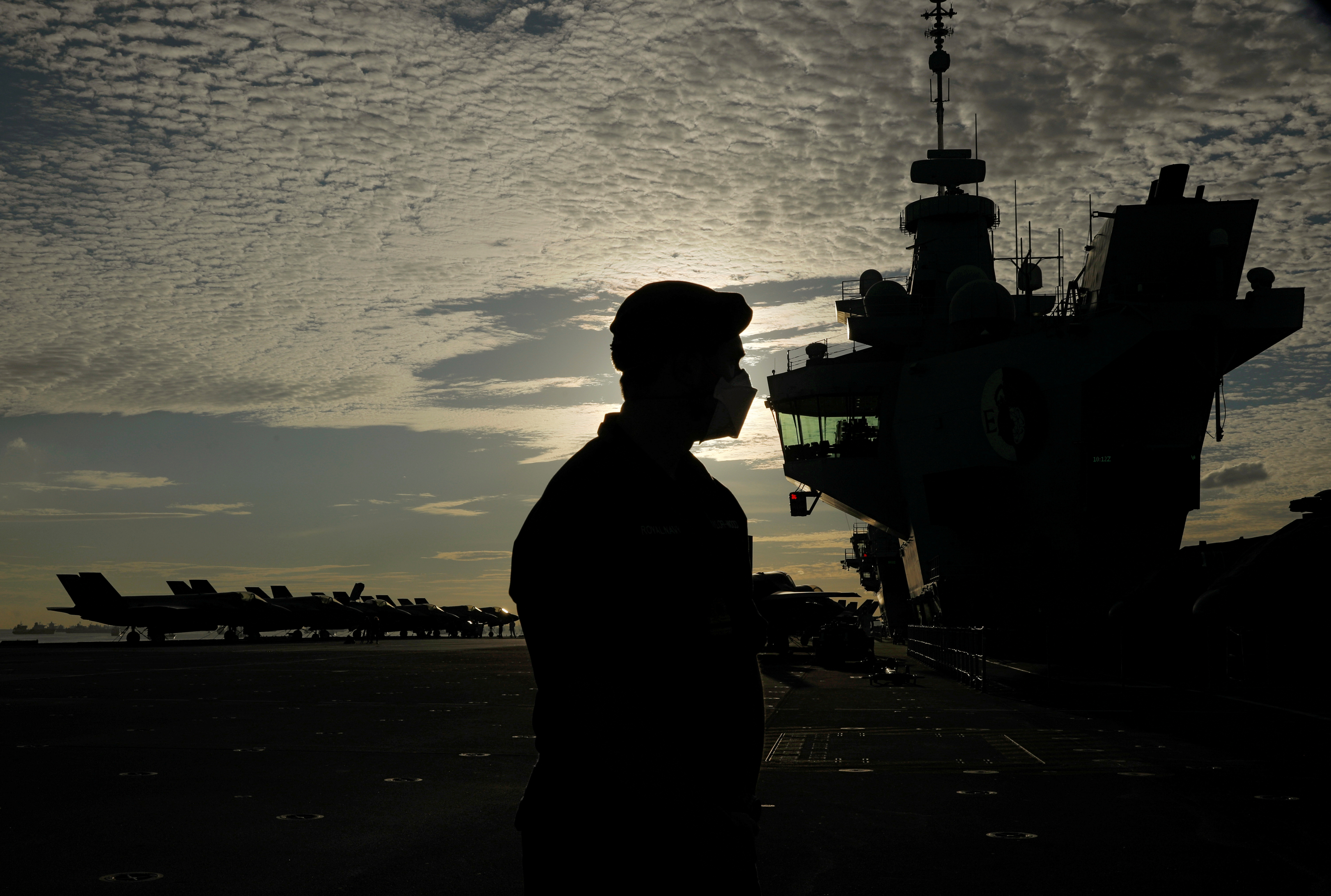 A member of navy personnel stands on the flight deck of Britain's HMS Queen Elizabeth aircraft carrier at Changi Naval Base in Singapore October 11, 2021. REUTERS/Edgar Su