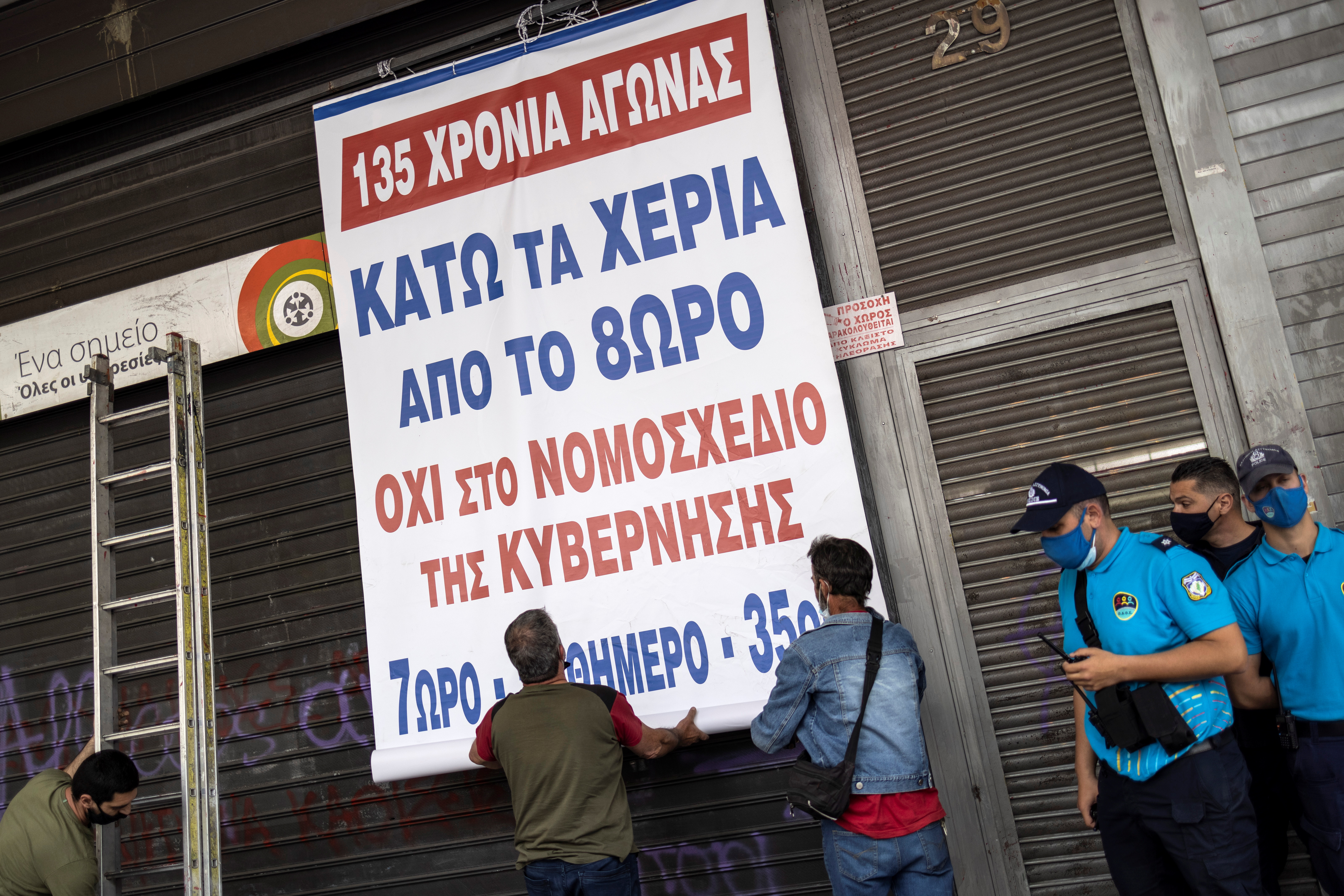 Members of the communist-affiliated trade union PAME hang a banner during a demonstration outside the Labour Ministry against a planned labour bill in Athens, Greece, May 12, 2021. The banner reads