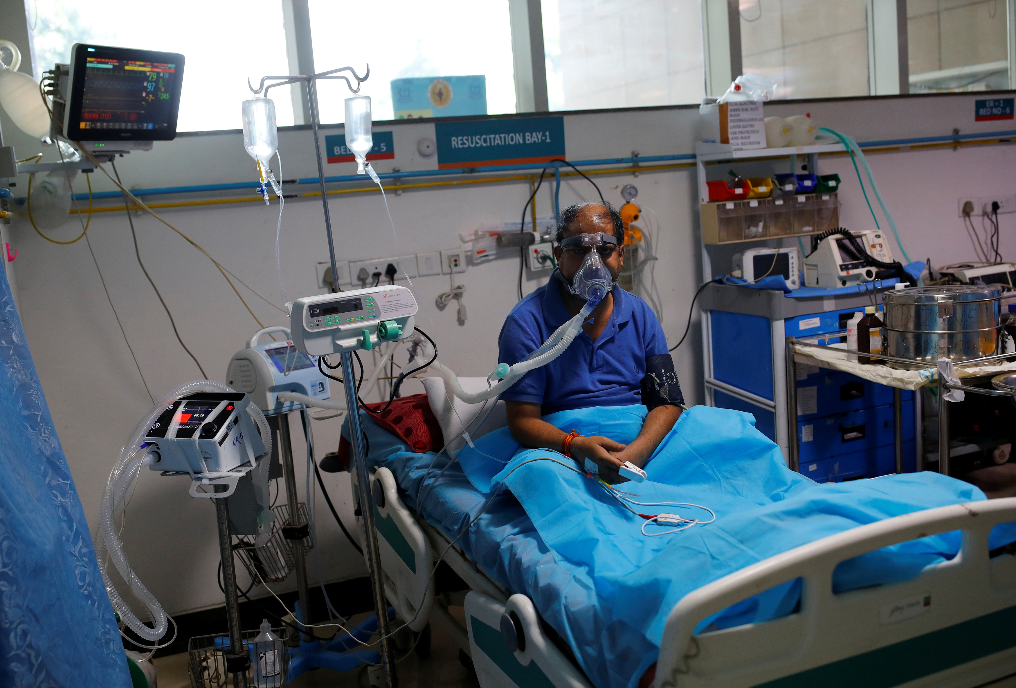 A man suffering from coronavirus disease (COVID-19), receives treatment as a Syringe Infusion Pump, donated by France is seen next to his bed, inside the emergency room of Safdarjung Hospital in New Delhi, India, May 7, 2021. REUTERS/Adnan Abidi