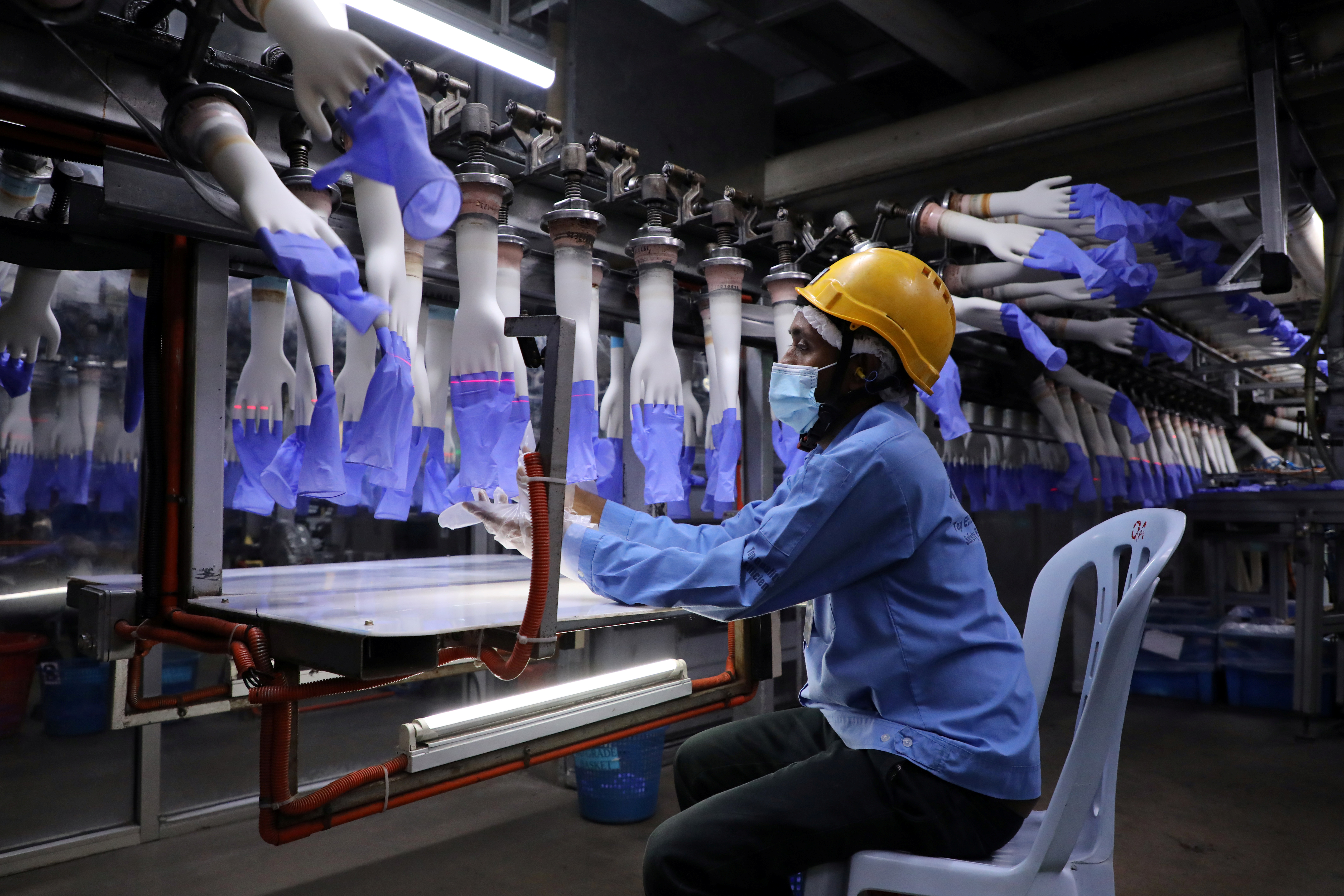 A worker inspects newly-made gloves at Top Glove factory in Shah Alam, Malaysia August 26, 2020. REUTERS/Lim Huey Teng