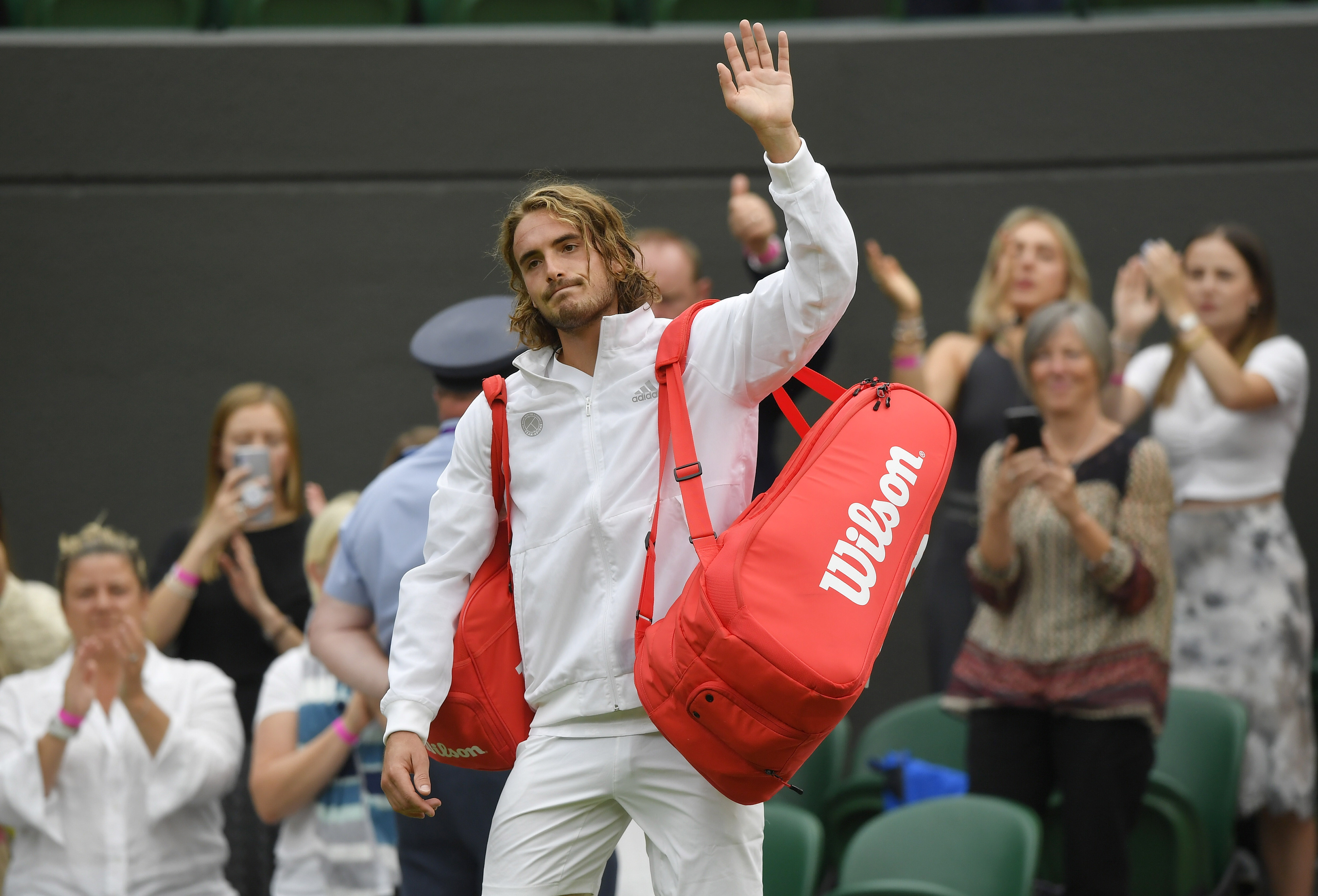 Tennis - Wimbledon - All England Lawn Tennis and Croquet Club, London, Britain - June 28, 2021 Greece's Stefanos Tsitsipas looks dejected as he waves after losing his first round match against Frances Tiafoe of the U.S. REUTERS/Toby Melville