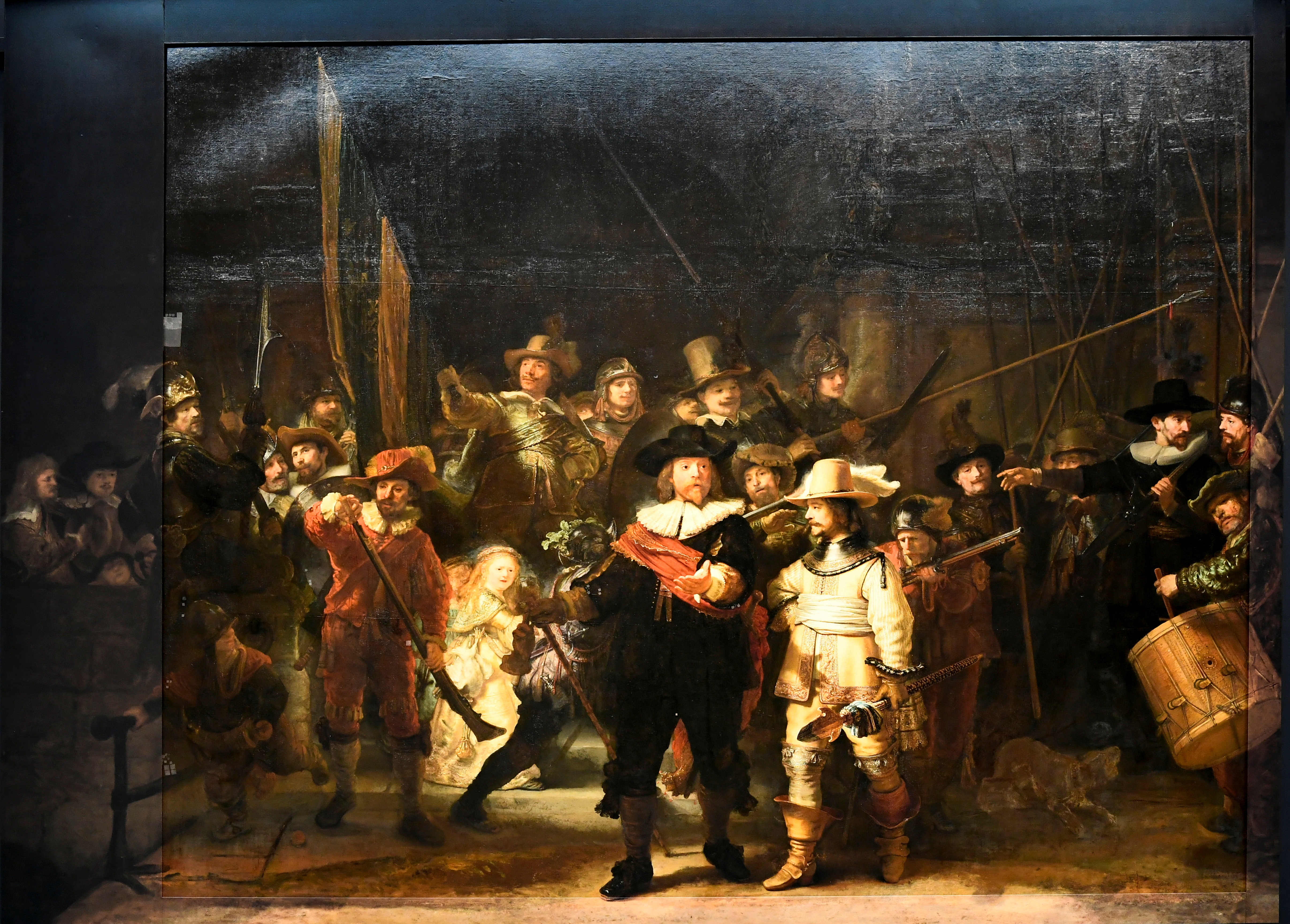 Rembrandt's famed Night Watch is seen back on display for the first time in 300 years, in what researchers say is its original size, with missing parts temporarily restored in an exhibition aided by artificial intelligence at Rijksmuseum in Amsterdam, Netherlands June 23, 2021. REUTERS/Piroschka van de Wouw