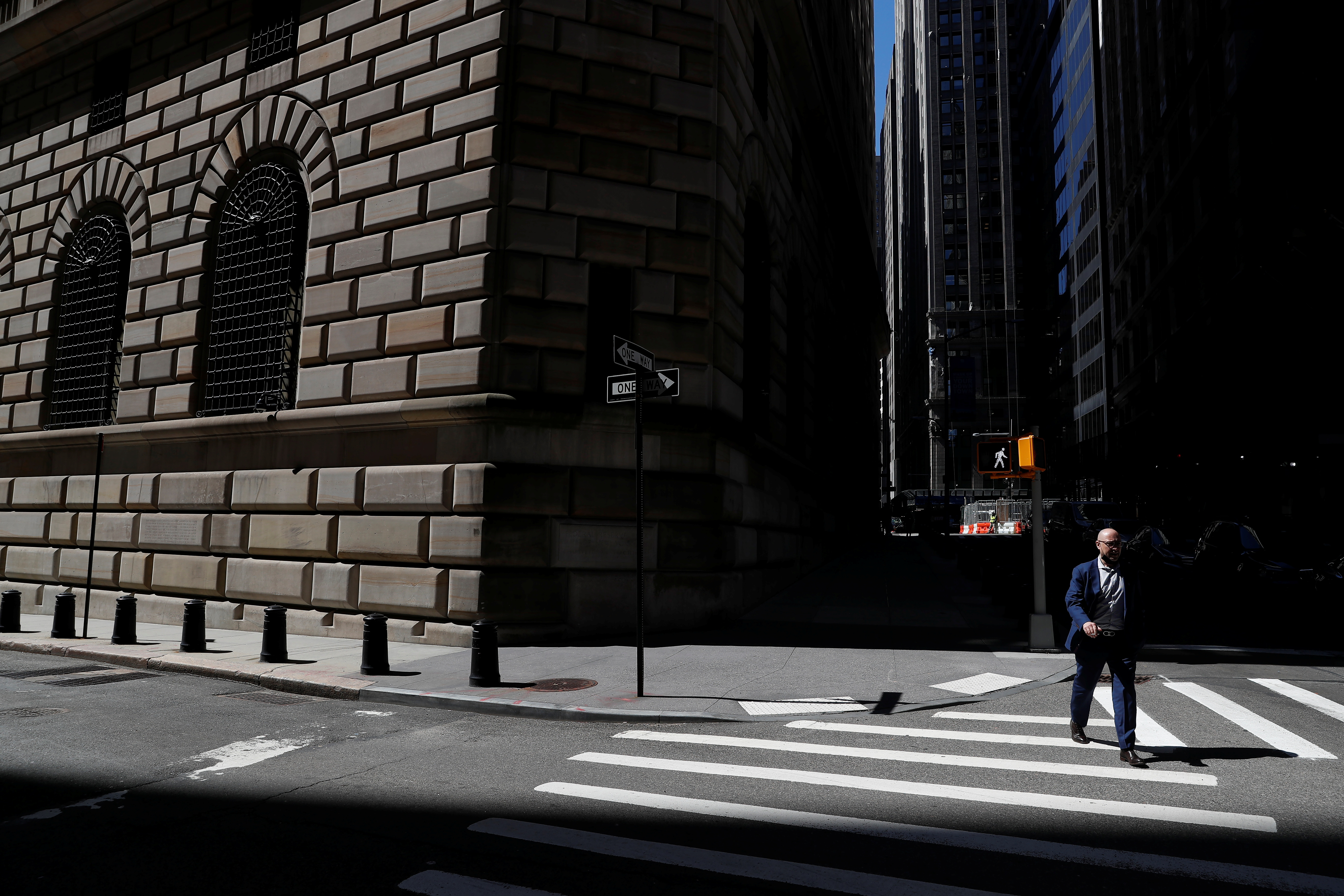 A man walks by the Federal Reserve Bank of New York Building in New York City, U.S., April 26, 2021. REUTERS/Shannon Stapleton