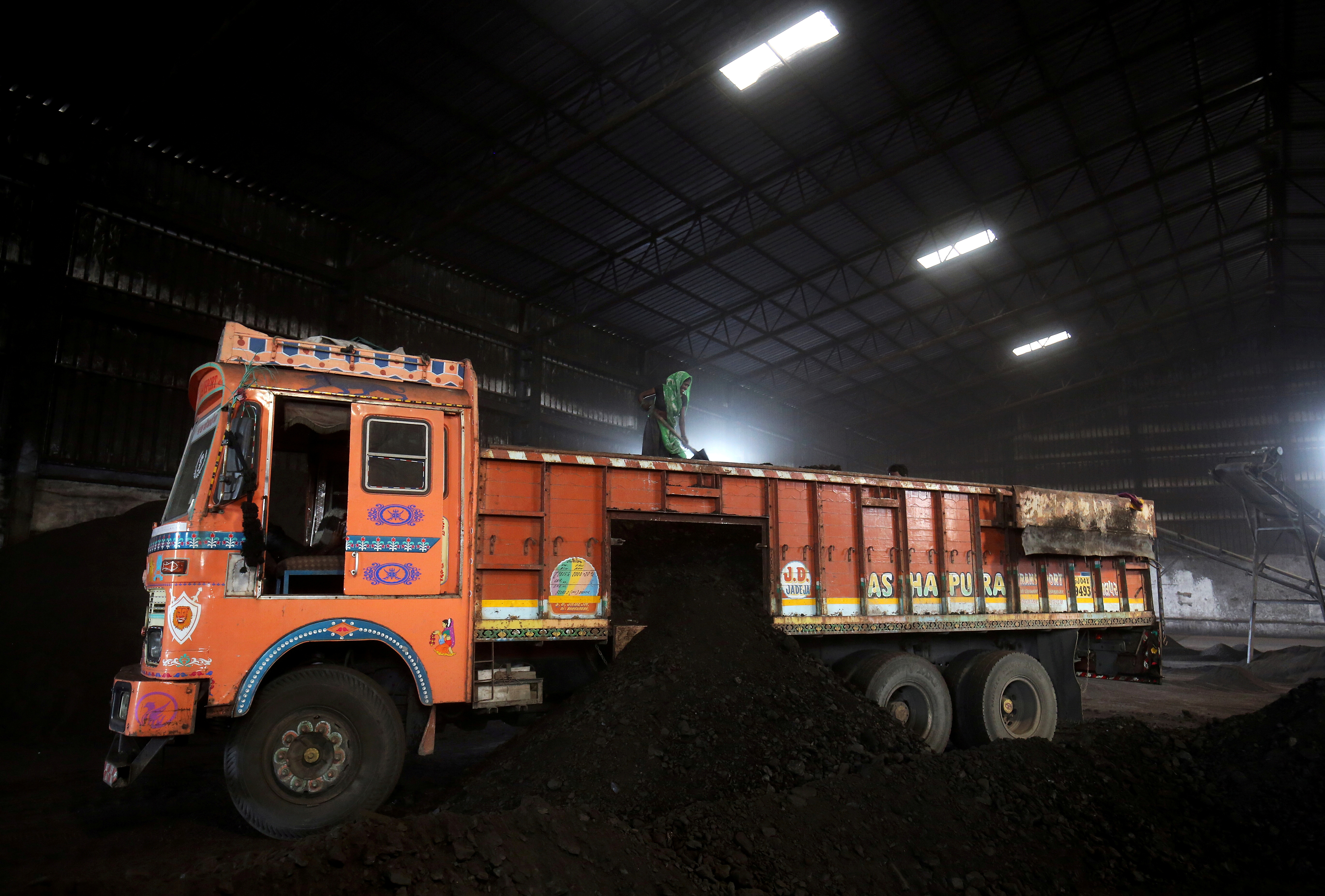 A worker shovels coal in a supply truck at a yard on the outskirts of Ahmedabad, India, October 25, 2018. REUTERS/Amit Dave