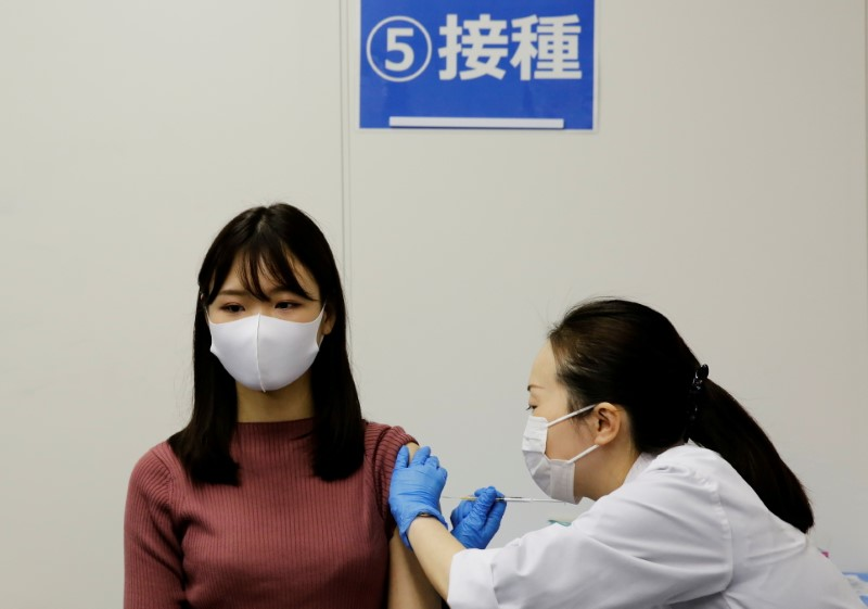 A staff of All Nippon Airways (ANA) receives a dose of the Moderna coronavirus disease (COVID-19) vaccine at the company's facility at Haneda airport in Tokyo, Japan June 14, 2021. REUTERS/Kim Kyung-Hoon