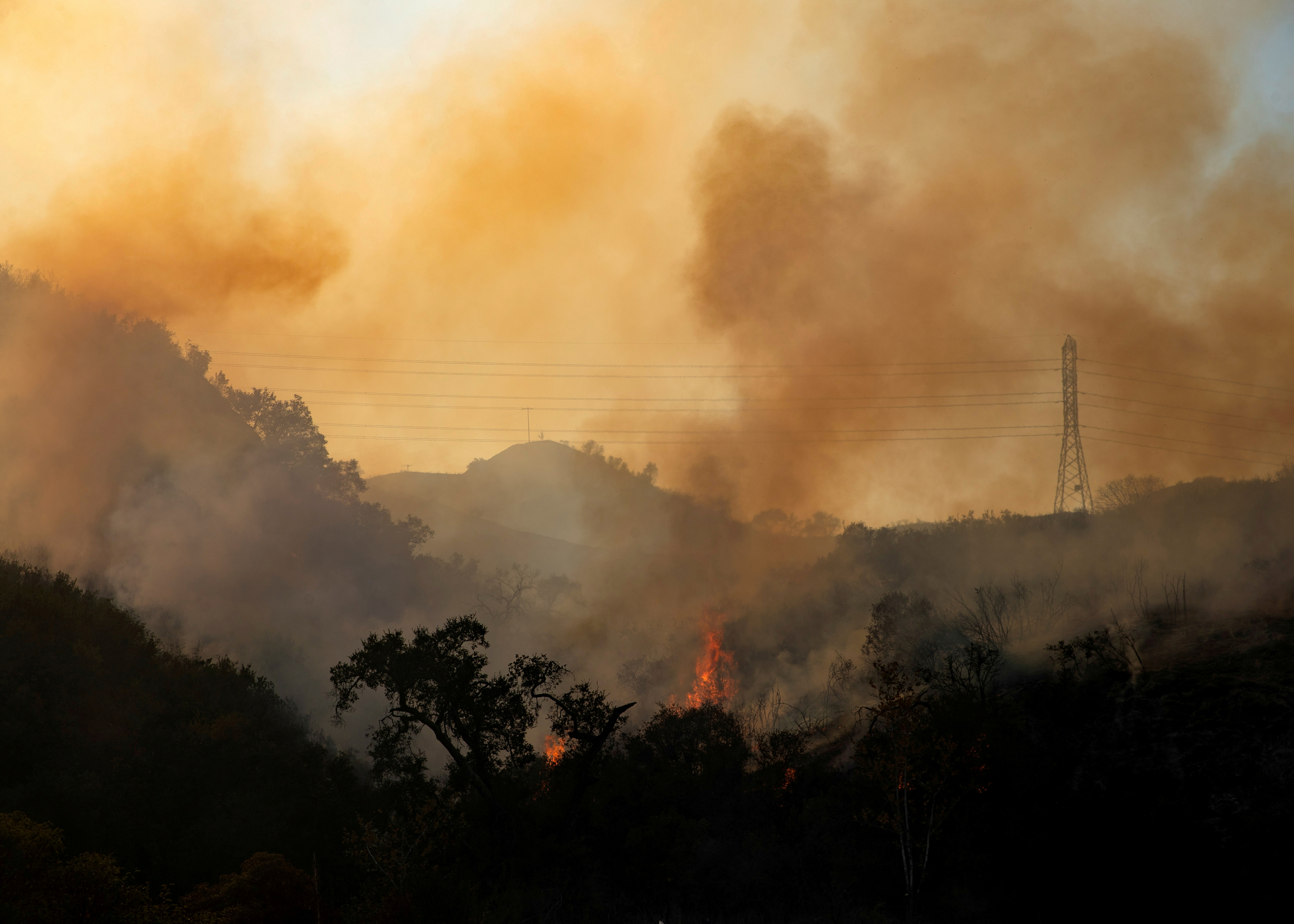 The Bond Fire wildfire burns next to electrical power lines near Modjeska Canyon, California, U.S., December 3, 2020.  REUTERS/Mike Blake