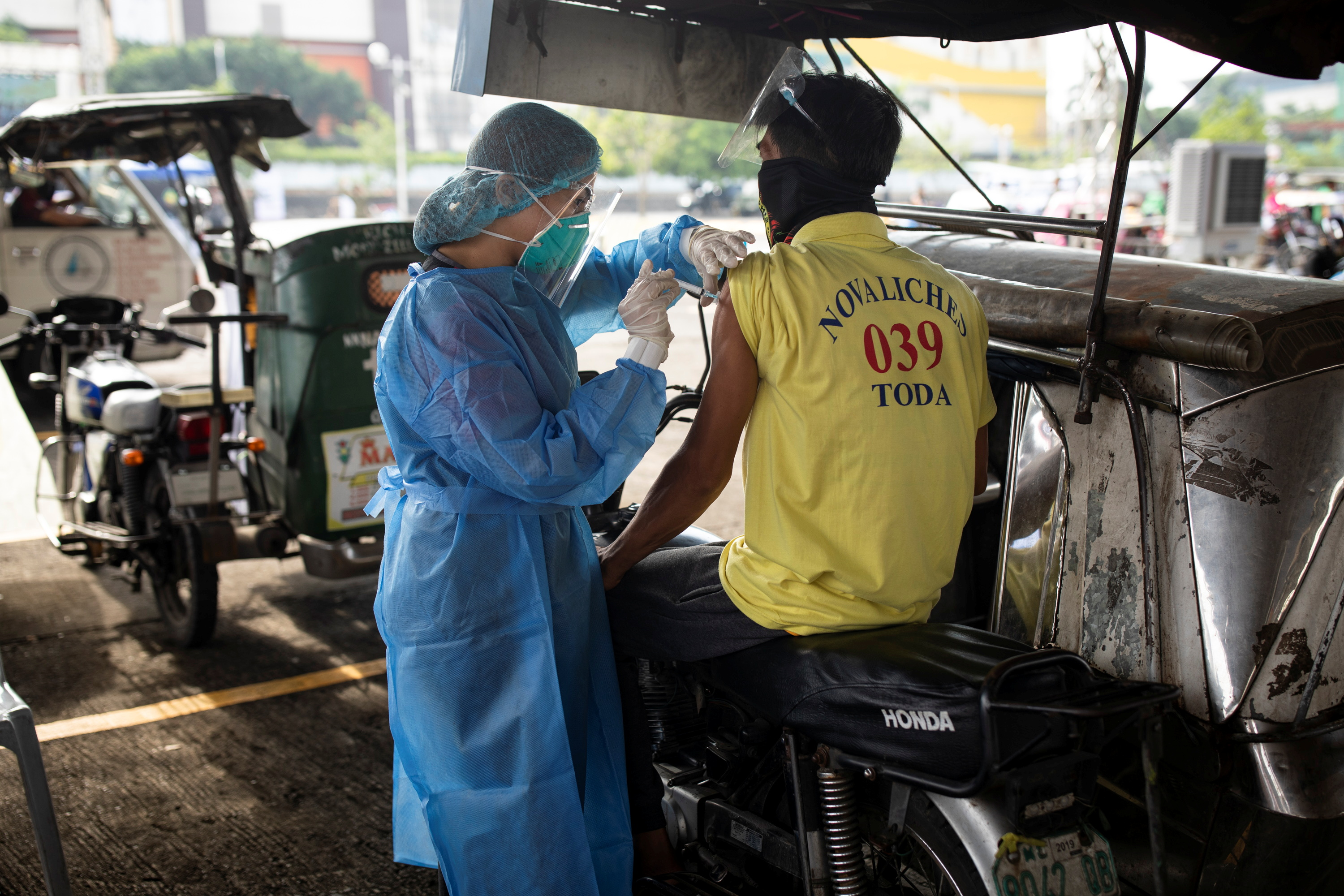 A health worker vaccinates a public transport driver with Sinovac COVID-19 vaccine in a shopping mall's parking lot turned into a drive-thru vaccination site, in Quezon City, Metro Manila, Philippines, August 13, 2021. REUTERS/Eloisa Lopez