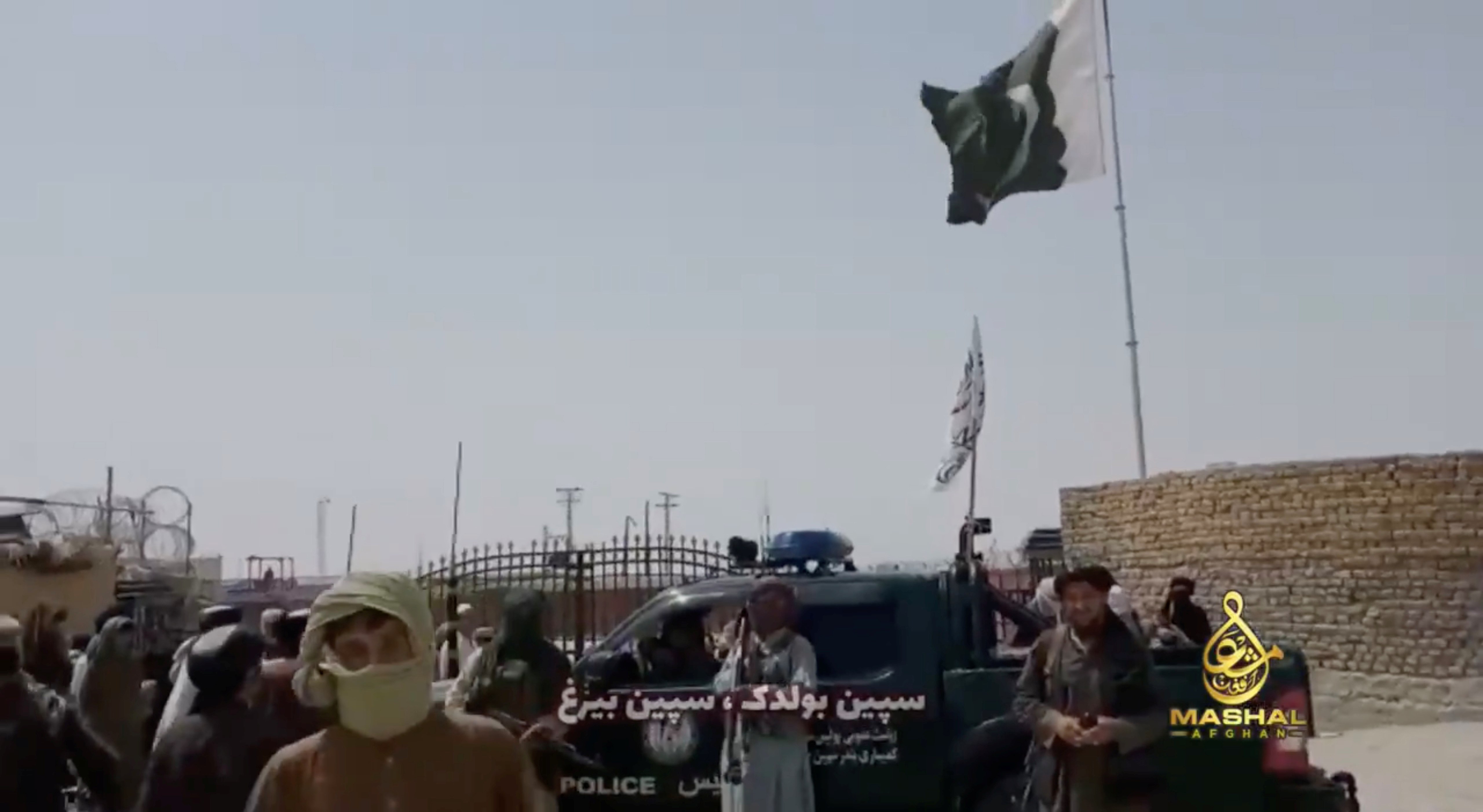 People stand in front of a vehicle as an Islamic Emirate of Afghanistan and a Pakistan's flag flutter in front of the friendship gate of Afghanistan and Pakistan at the Wesh-Chaman border crossing, Spin Boldak, Afghanistan July 14, 2021, in this screen grab obtained from a video. TALIBAN HANDOUT via REUTERS THIS IMAGE HAS BEEN SUPPLIED BY A THIRD PARTY.