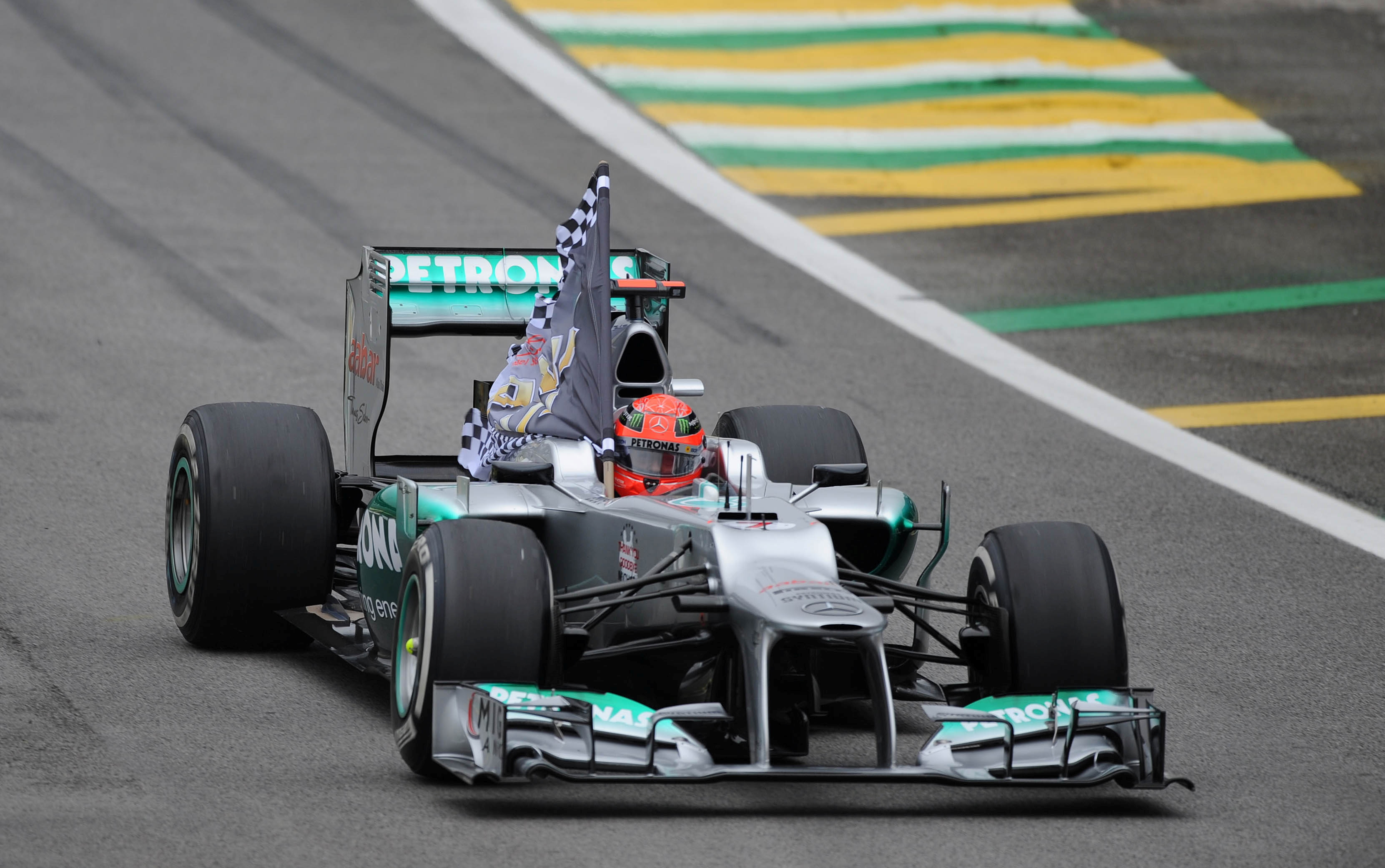Formula One - F1 - Brazilian Grand Prix 2012 - Autodromo Jose Carlos Pace, Sao Paulo, Brazil  - 25/11/12   Mercedes' Michael Schumacher holds a flag after finishing his last f1 race   Mandatory Credit: Action Images / Crispin Thruston   Livepic