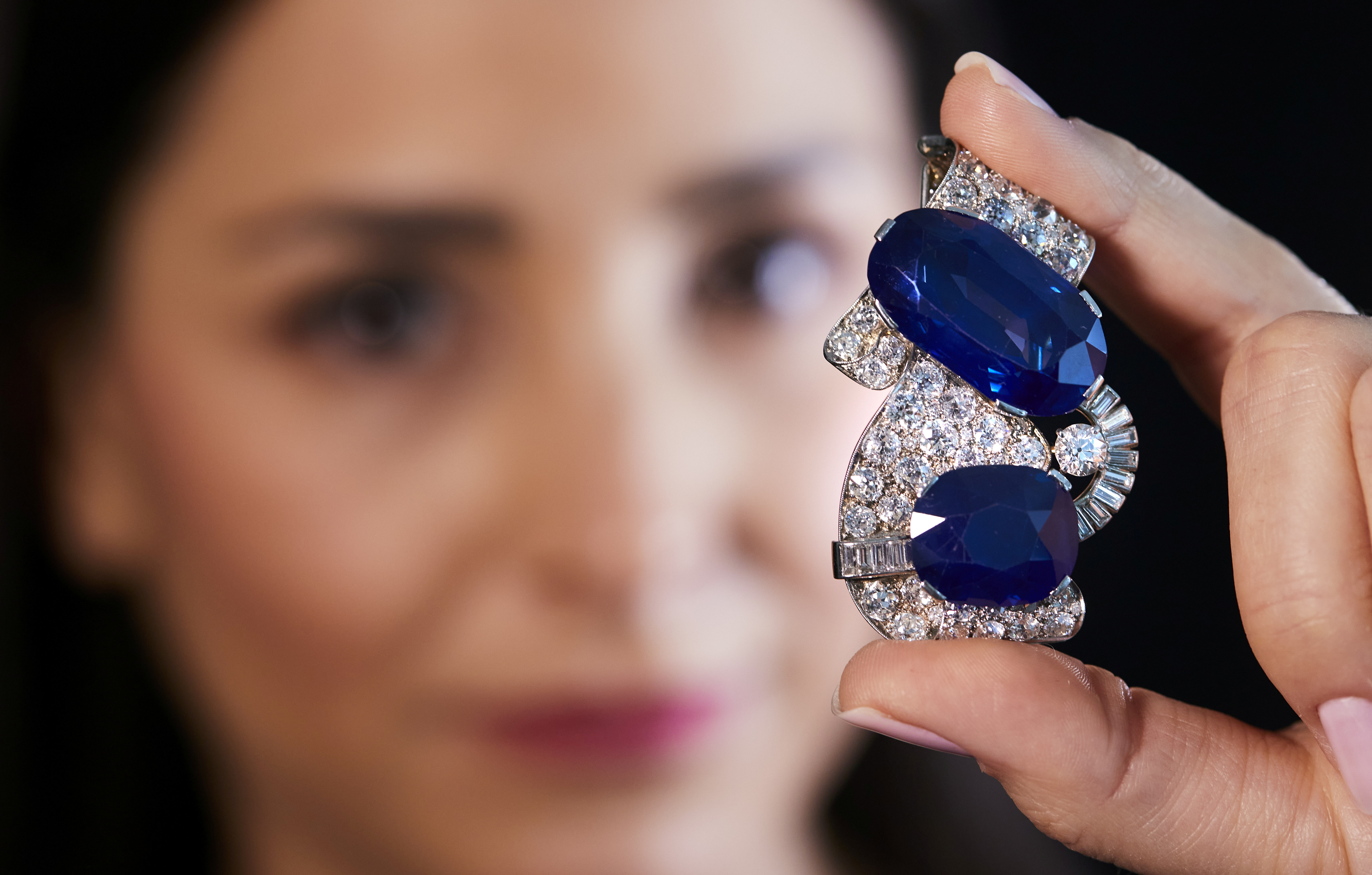 A staff holds a 1930s sapphire and diamond brooch, featuring the largest Kashmir sapphire ever to appear at auction, during a preview at Sotheby's before their auction in Geneva, Switzerland, May 6, 2021.  REUTERS/Denis Balibouse